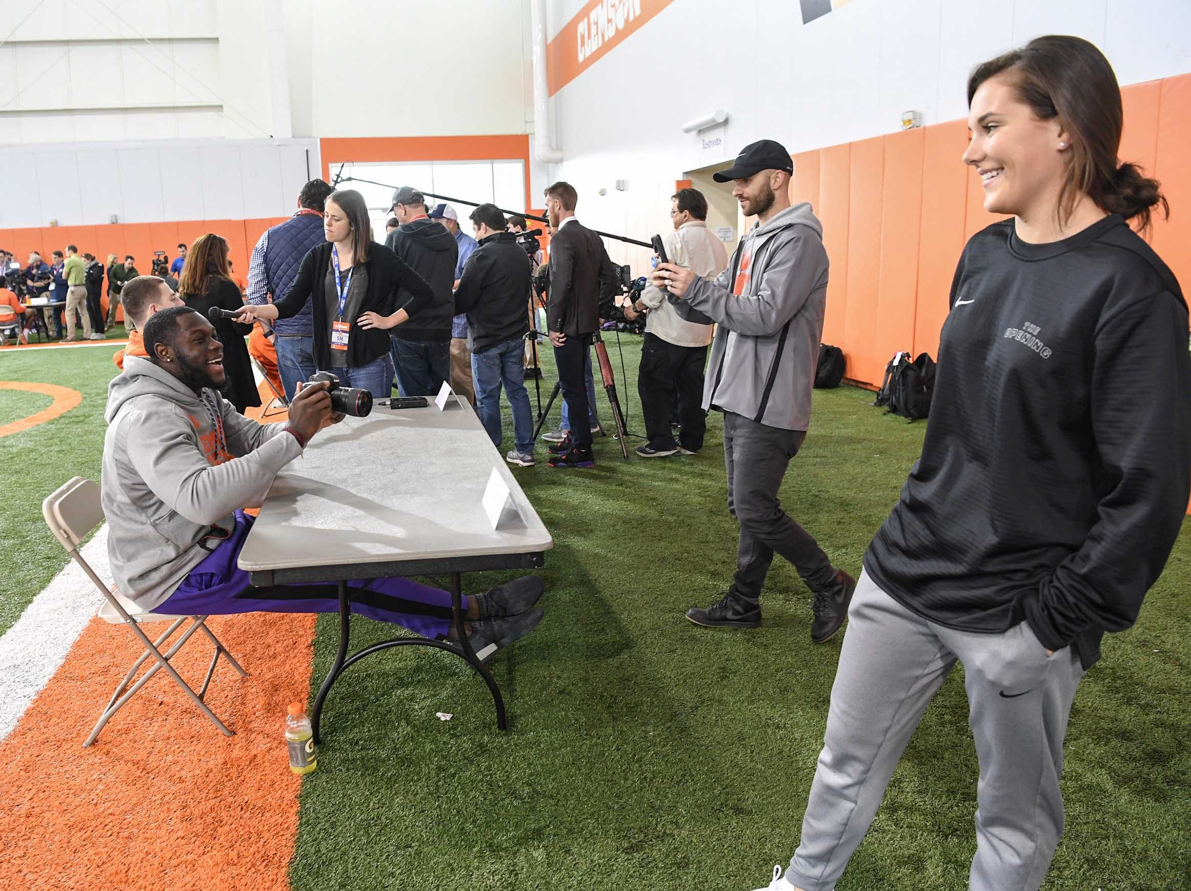 Clemson tight end Milan Richard takes a moment to get a photo of reporter Maddie Williams, right, with her camera a student at Clemson, during media day in the Poe Indoor Facility in Clemson Wednesday, January 2, 2019.