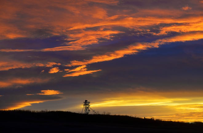 The top of the AgriTech Park grain elevator against a colorful sunset in December, the windiest month of the year in Great Falls.