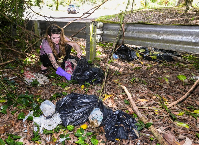 Yona resident Chloe Conrad checks the contents of decomposing material discarded at the Sella Bay Overlook parking lot on Wednesday, Jan. 2, 2019. Conrad reported to authorities that the garbage bags contained the bodies of dogs.