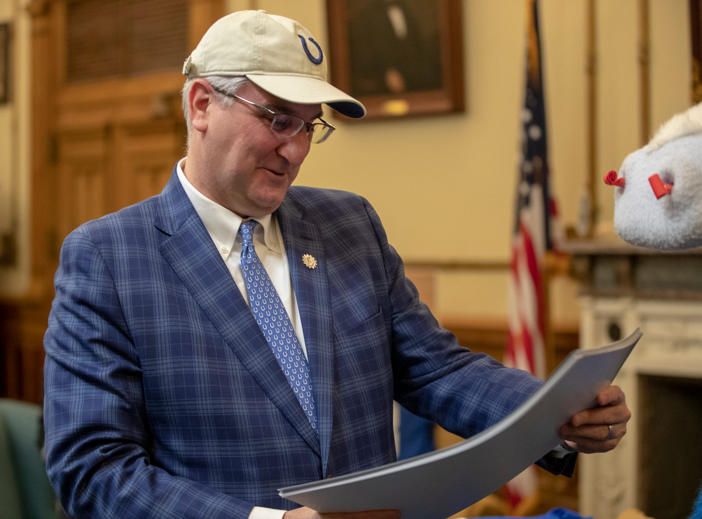 Indiana Governor Eric Holcomb looks at pro Colts banners that were just delivered to his office by mascot Blue. at the Indiana Statehouse, Indianapolis, Wednesday, January 3, 2019.