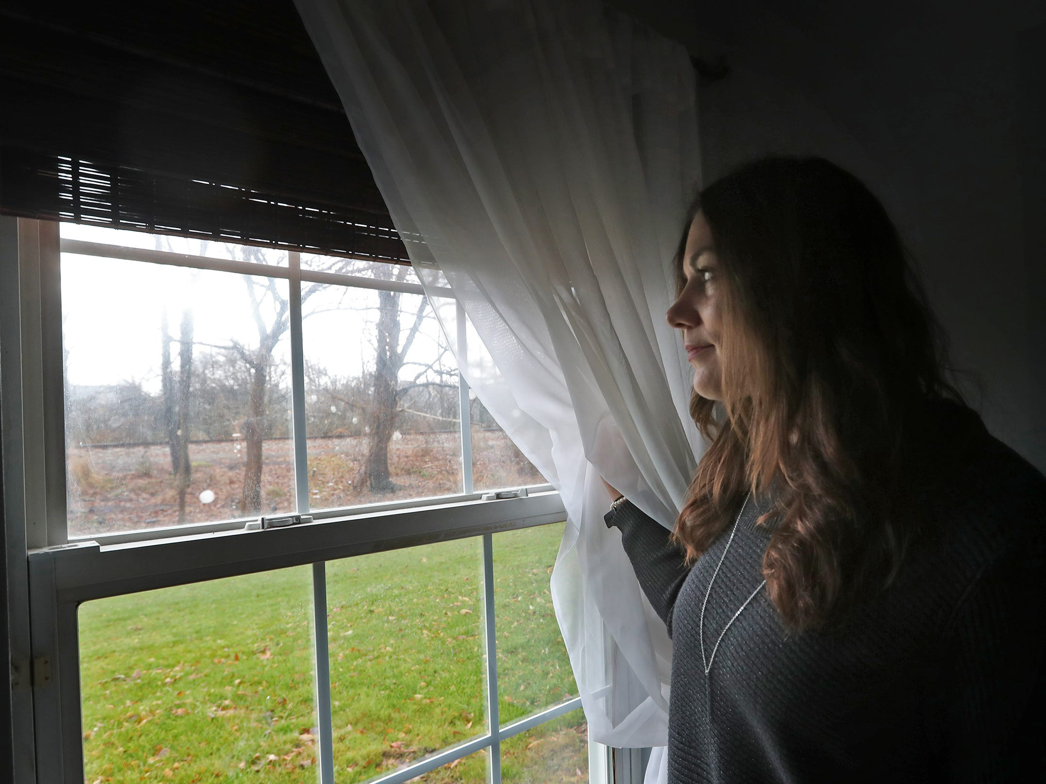 "Marcy Kellar looks out the bedroom window of her Fishers home, toward the Nickel Plate railroad tracks, Monday, Dec. 31, 2018.  She worries about her loss of privacy and the loss of her garden that fills her with joy, when a trail is built along the track.  The first thing Kellar sees when she wakes up is her garden.  When the leaves are full and everything is in bloom, it looks like a fairy garden, she says.   ""The amount of happiness it gives me,"" she adds tearily, ""I don't want that to go away,"""