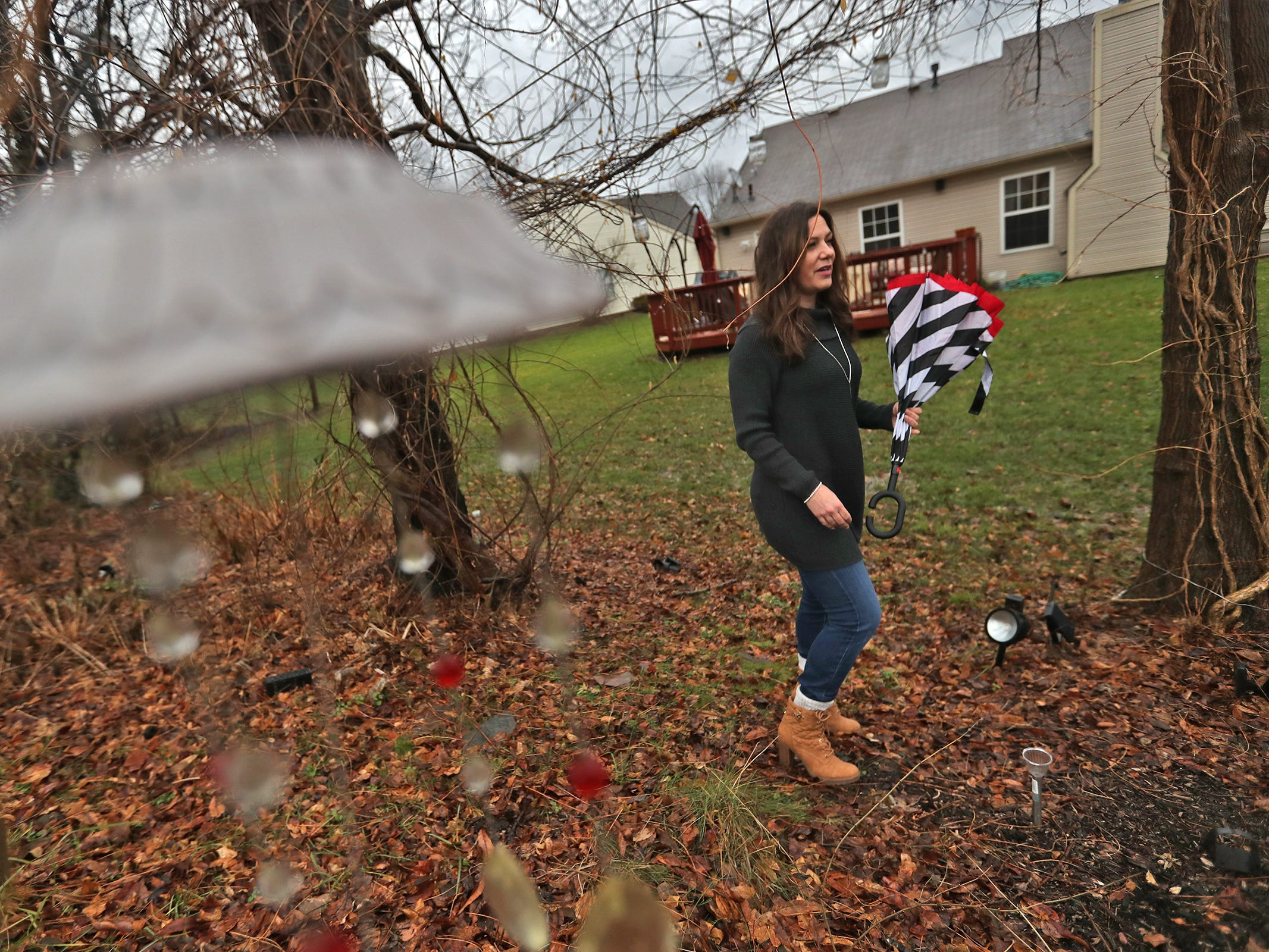 Marcy Kellar stands in her back yard in Fishers along the Nickel Plate railroad tracks, Monday, Dec. 31, 2018.  She worries about her loss of privacy and the loss of her garden that fills her with joy, when a trail is built along the track.  She plants lots of flowers and greenery, and fills her garden with solar-powered lights and art.