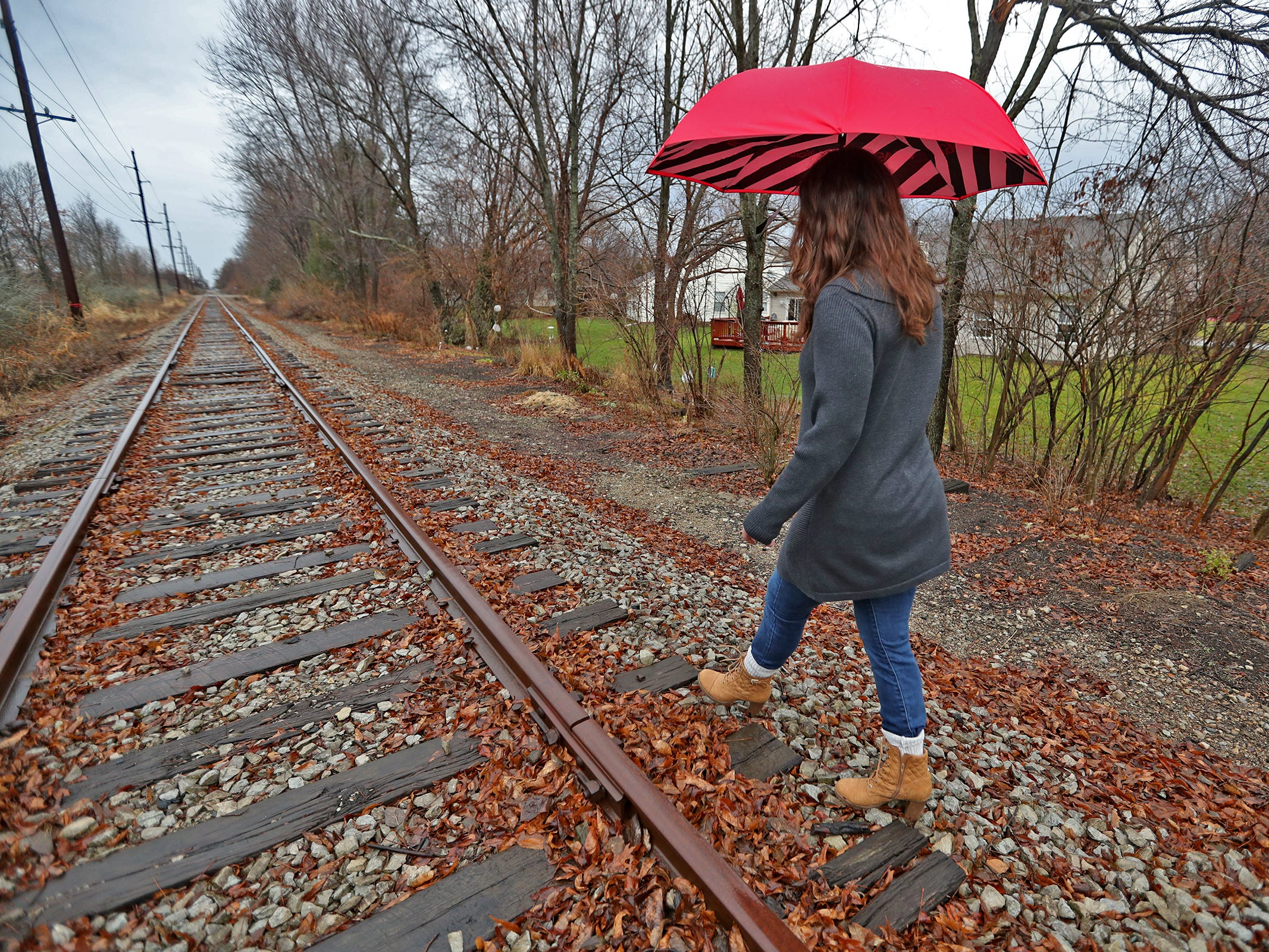 Marcy Kellar walks along the Nickel Plate railroad tracks behind her Fishers home, Monday, Dec. 31, 2018.  She worries about her loss of privacy and the loss of her garden that fills her with joy, when a trail is built along the track.