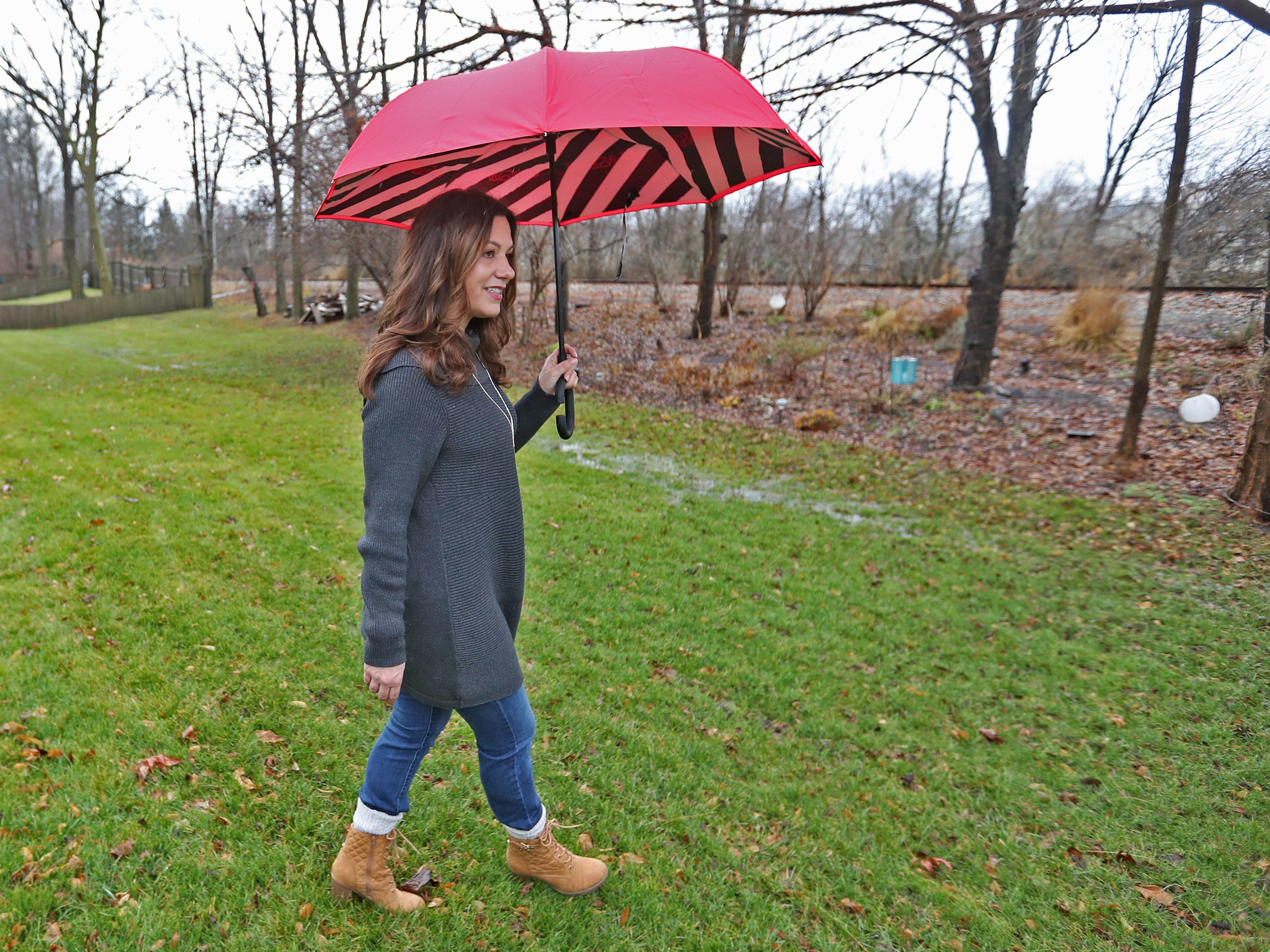 Marcy Kellar walks in her back yard toward the Nickel Plate railroad tracks behind her Fishers home, Monday, Dec. 31, 2018.  She worries about her loss of privacy and the loss of her garden that fills her with joy, when a trail is built along the track.