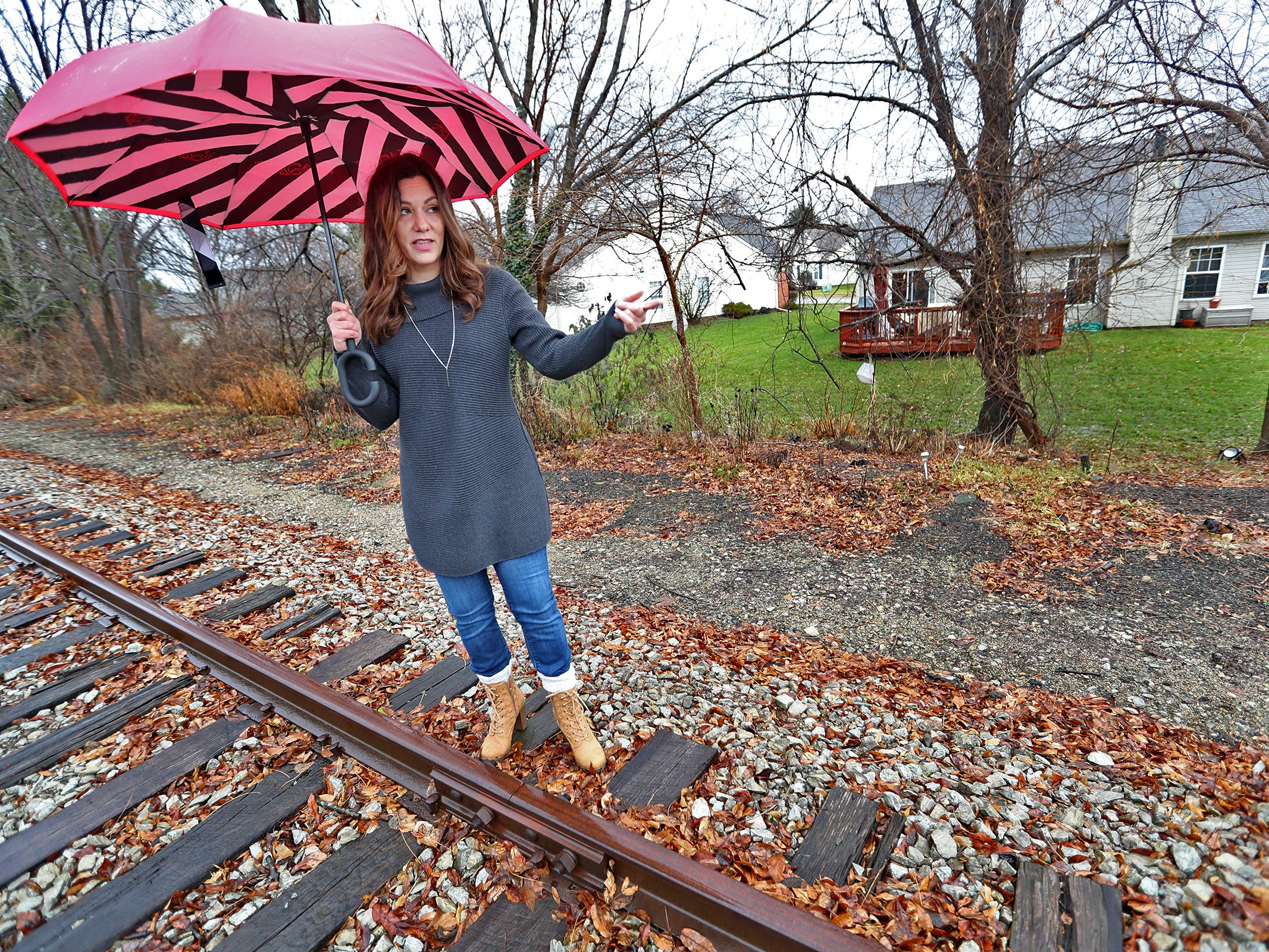 Marcy Kellar stands along the Nickel Plate railroad tracks behind her Fishers home, Monday, Dec. 31, 2018.  She worries about her loss of privacy and the loss of her garden that fills her with joy, when a trail is built along the track.
