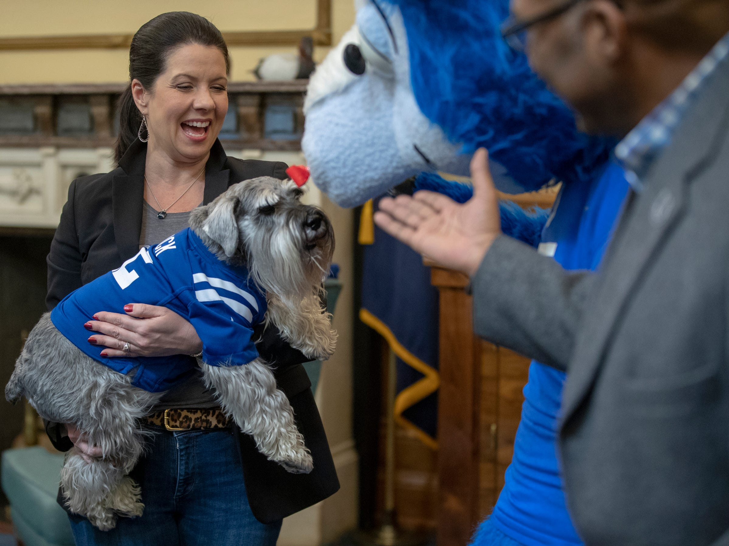Janet Holcomb holds her family dog Henry, during a visit by Blue, the Colts mascot to the Indiana Statehouse, Indianapolis, Wednesday, January 3, 2019.