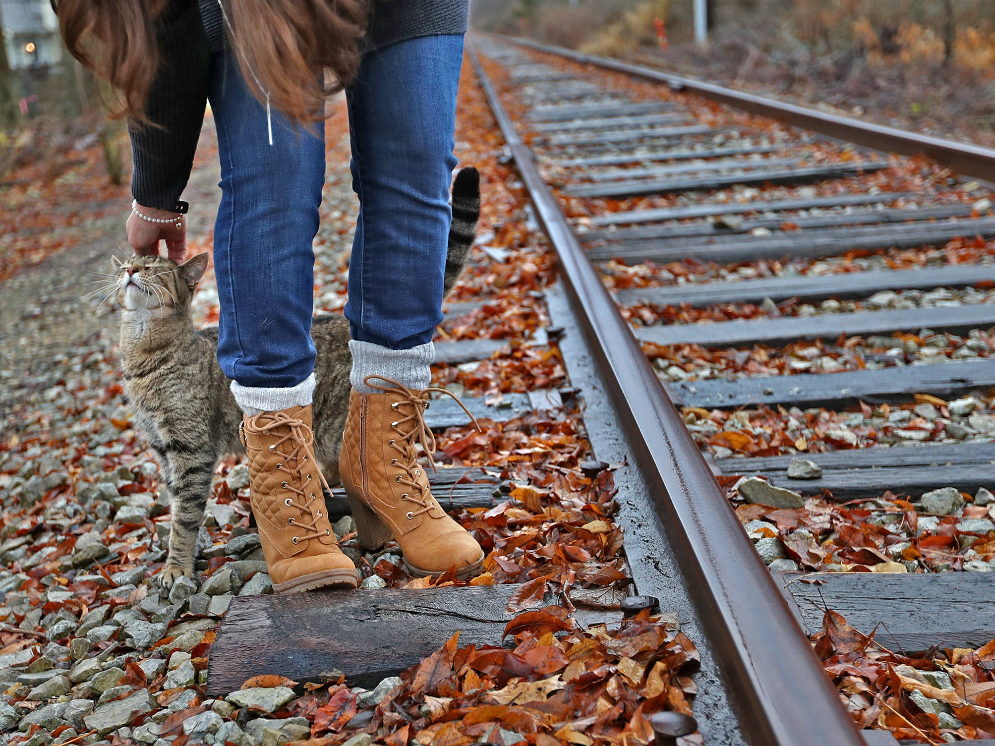 Marcy Kellar pets her cat as she stands along the Nickel Plate railroad tracks behind her Fishers home, Monday, Dec. 31, 2018.  She worries about her loss of privacy and the loss of her garden that fills her with joy, when a trail is built along the track.