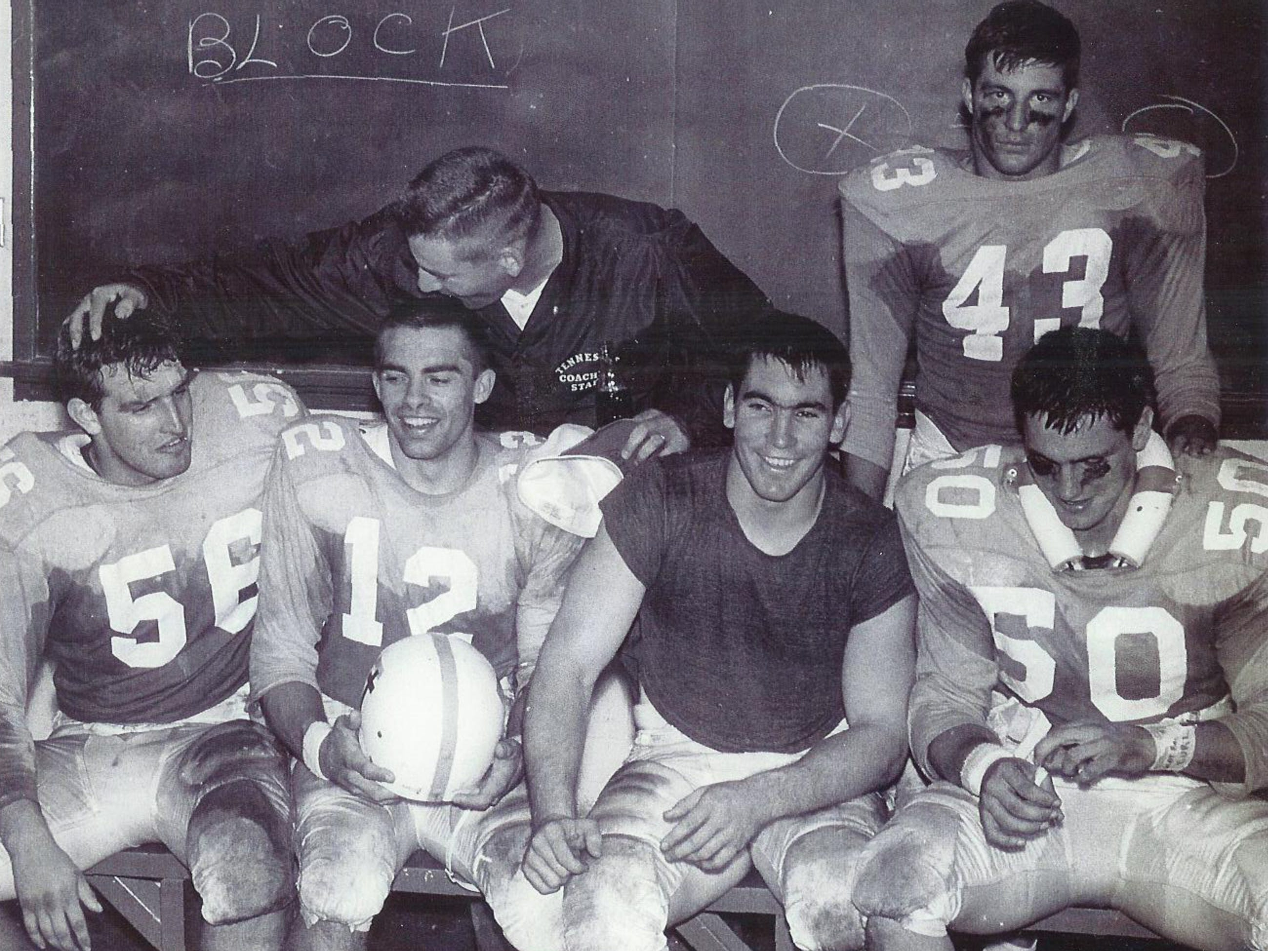 Coach Doug Dickey congratulates center Reggie Jellicorse (56), quarterback Charlie Fulton (12), fullback Stan Mitchell, linebacker Frank Emanuel (50), and defensive back Harold Stancell (43) after a victorious effort against Georgia Tech on Nov. 6, 1965.