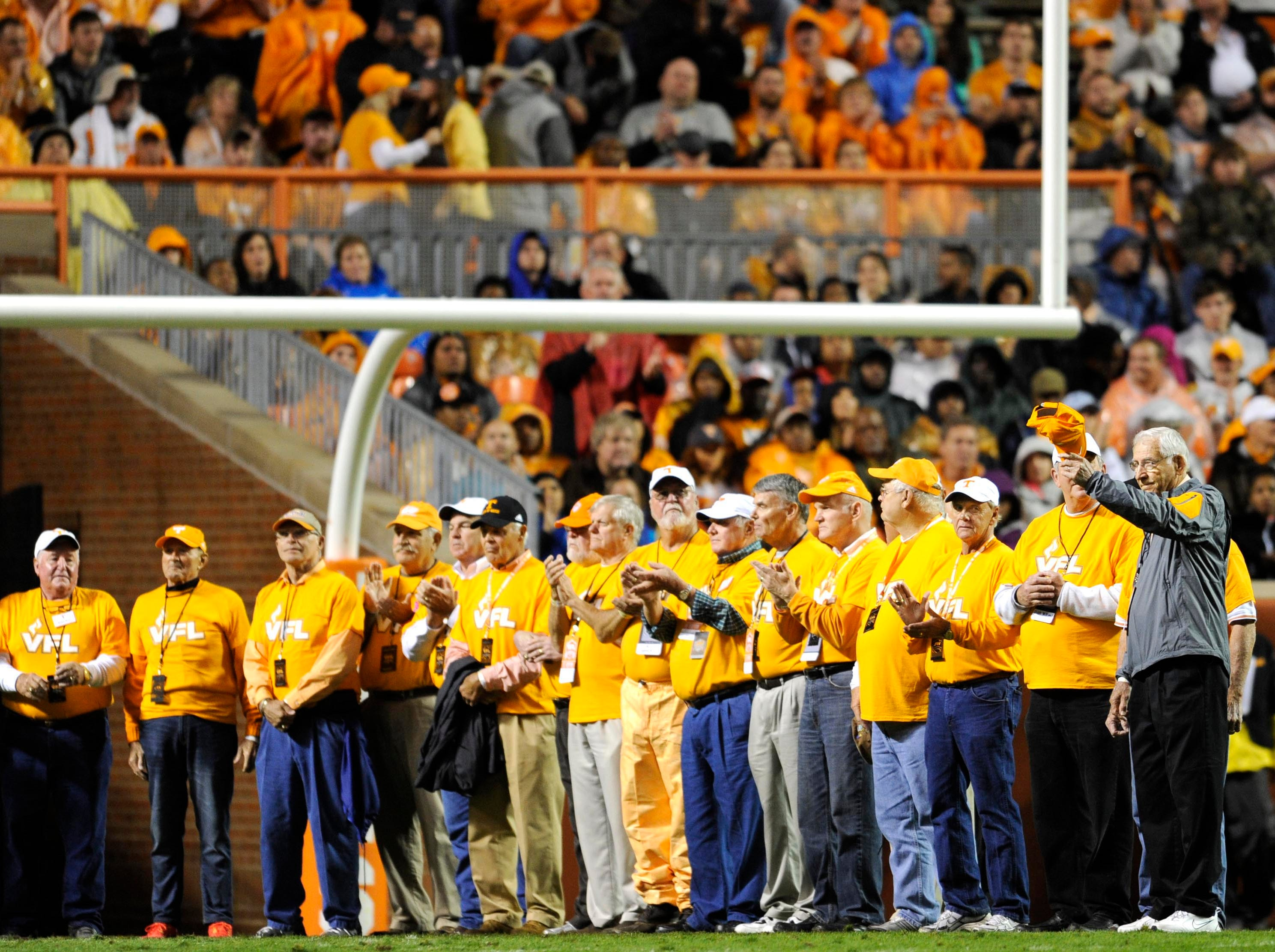 Doug Dickey, former Tennessee football coach, right, waves his cap to acknowledge the crowd as he stands on the field with former players during the first half against Arkansas at Neyland Stadium in Knoxville, Tenn. on Saturday, Oct. 3, 2015.