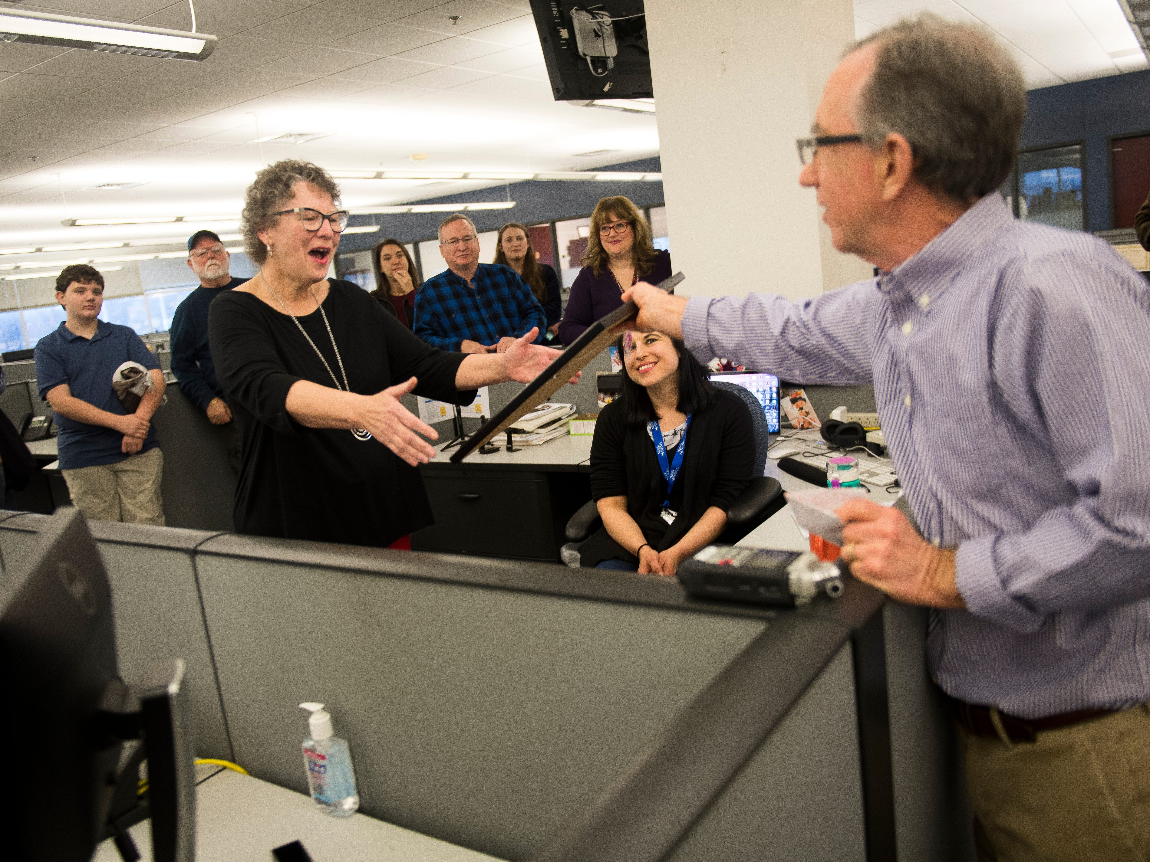 Features writer Mary Constantine, left, is handed a custom Charlie Daniel cartoon by executive editor Jack McElroy, right, during a retirement party on Wednesday, January 2, 2019. The Knoxville News Sentinel celebrated the retirements of Mary Constantine, Jack Lail and Michael Patrick.