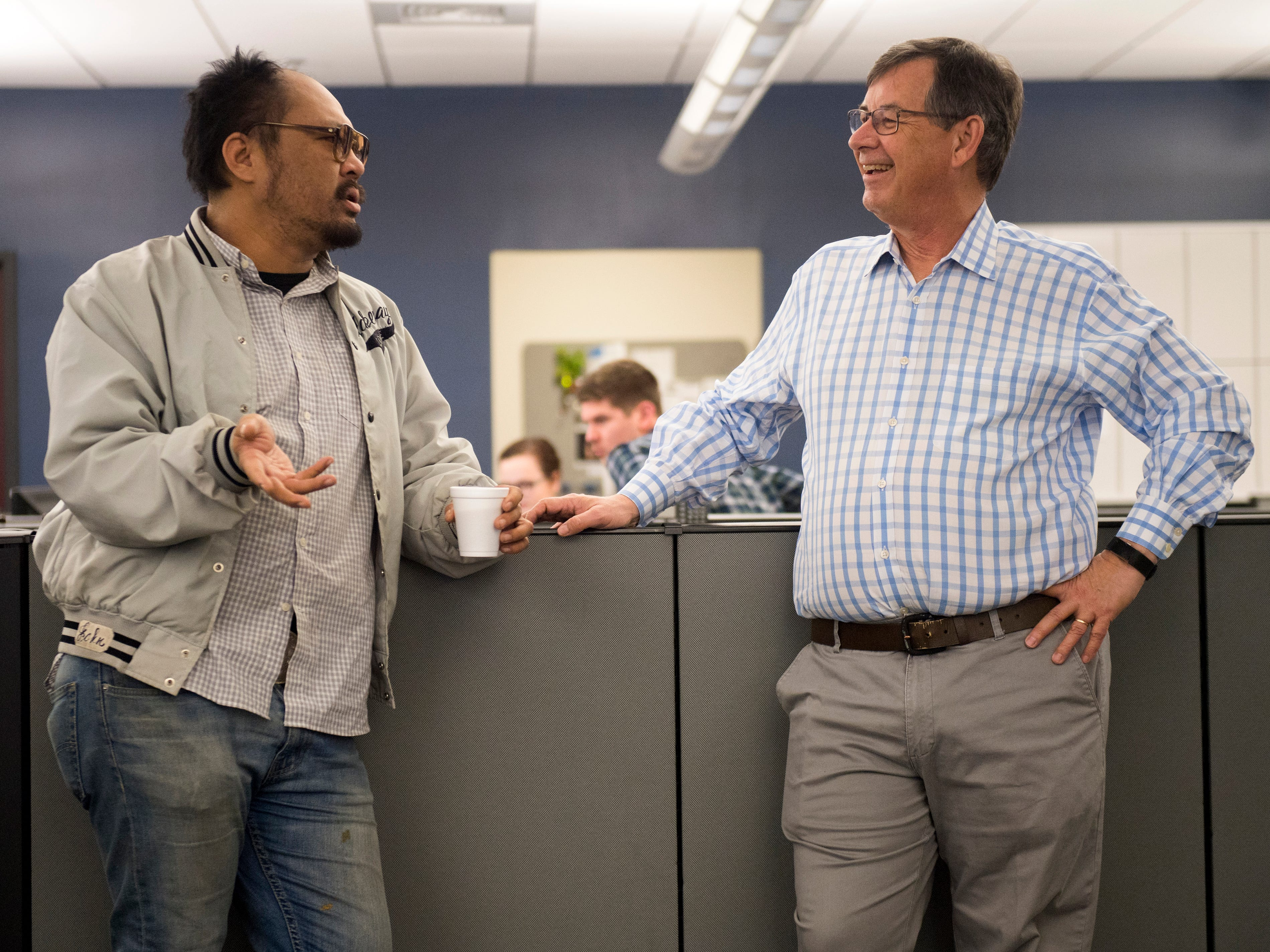 Photographer Saul Young, left, shares a story with Consumer Experience Director Jack Lail in the Knoxville News Sentinel's newsroom on Wednesday, January 2, 2019. The Knoxville News Sentinel celebrated the retirements of Mary Constantine, Jack Lail and Michael Patrick.