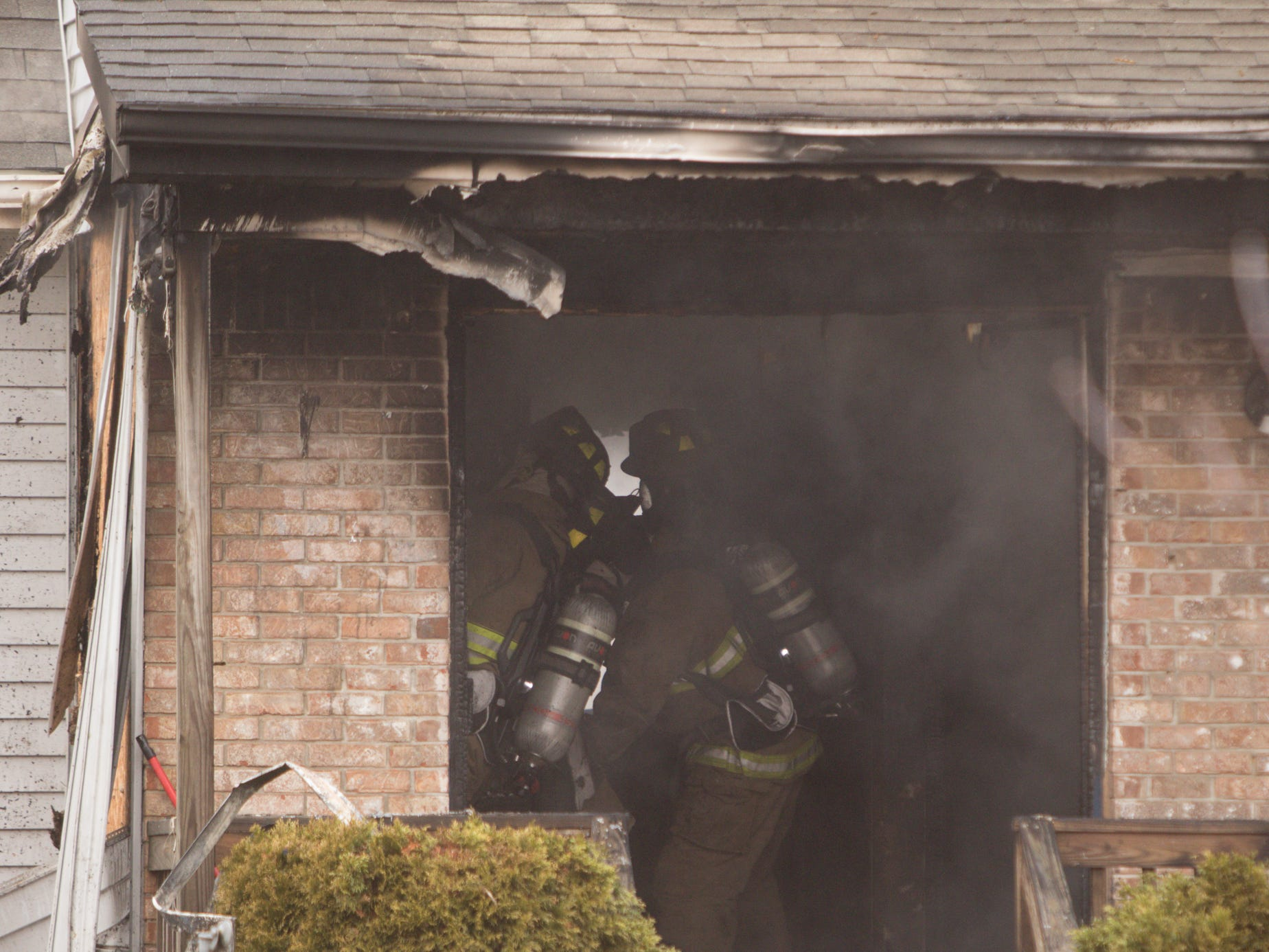 Firefighters convene inside after breaking out the doorwall of the home on Norton Rd. Wednesday, Jan. 2, 2019.