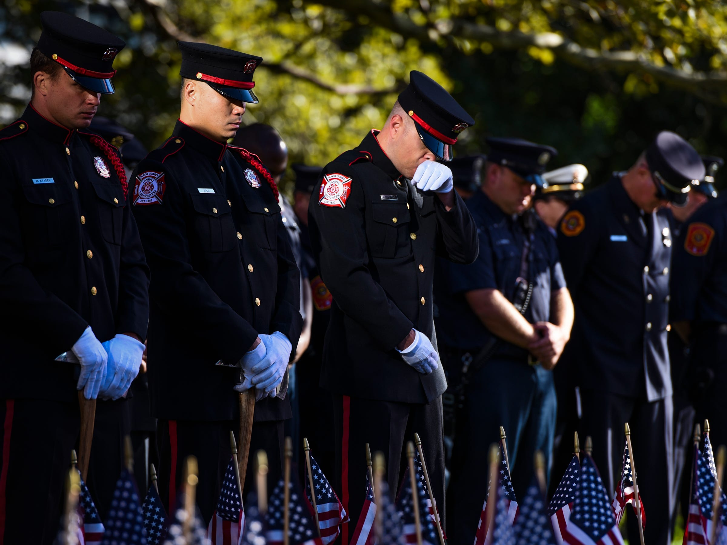A member of the Lansing Fire Department reacts during a moment of silence honoring fallen comrade Dennis Rodeman, who died in the line of duty Sept. 9, 2016.  Hundreds gathered Tuesday morning at the 9/11 Memorial in downtown Lansing, marking 17 years since the 9/11 attacks.  [AP Photo/Matthew Dae Smith/Lansing State Journal]