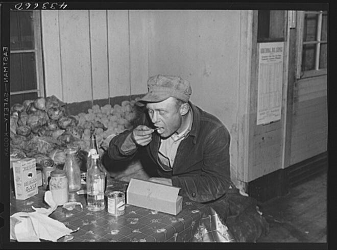 This 1941 black-and-white photograph shows a worker eating dinner at a crossroads store in Manchester, North Carolina.