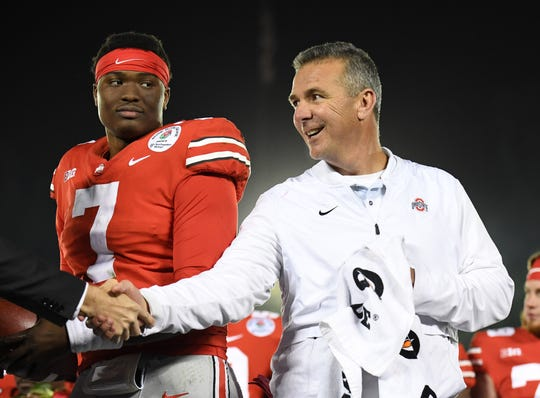 Ohio State coach Urban Meyer and quarterback Dwayne Haskins celebrate on the podium after the Buckeyes defeat Washington 28-23 in the Rose Bowl.