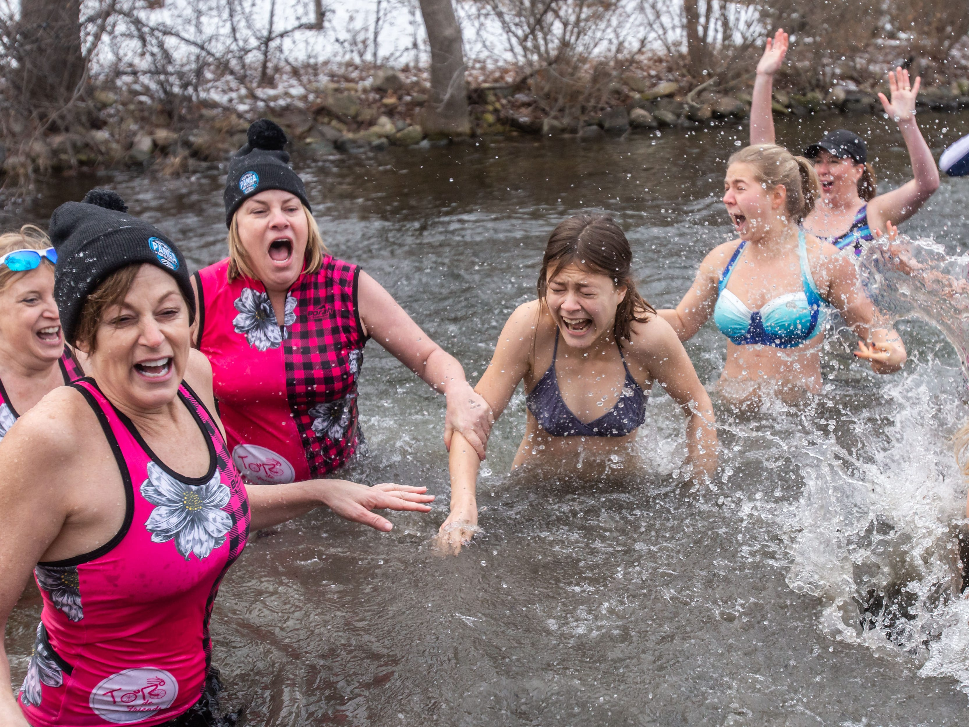 Jumpers react to the frigid water of Upper Nemahbin Lake during the annual Polar Plunge at Panga Bar & Grill in Oconomowoc on Tuesday, Jan. 1, 2019. Funds raised from this year's plunge will benefit research efforts of the Alzheimer's Association.