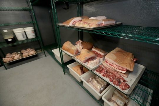 Berkshire pork fattened on whey sits in the storage cooler in the new La Merenda Market.