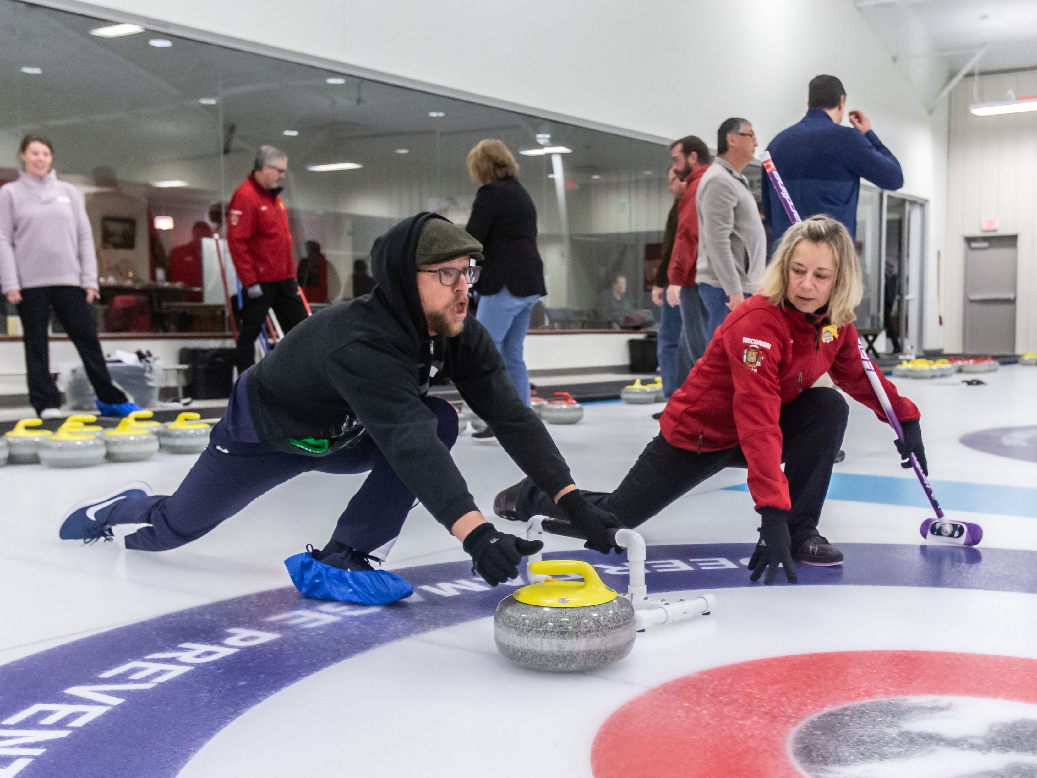 Matt Wills of Whitefish Bay releases a stone as instructor Chris Korjenek offers advice during the Learn to Curl program at the Milwaukee Curling Club in Cedarburg on Saturday, Dec. 29, 2018.