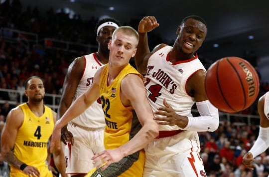 St. John's guard Mustapha Heron and Marquette forward Joey Hauser chase the ball in the teams' Jan. 1 matchup at Carnesecca Arena.