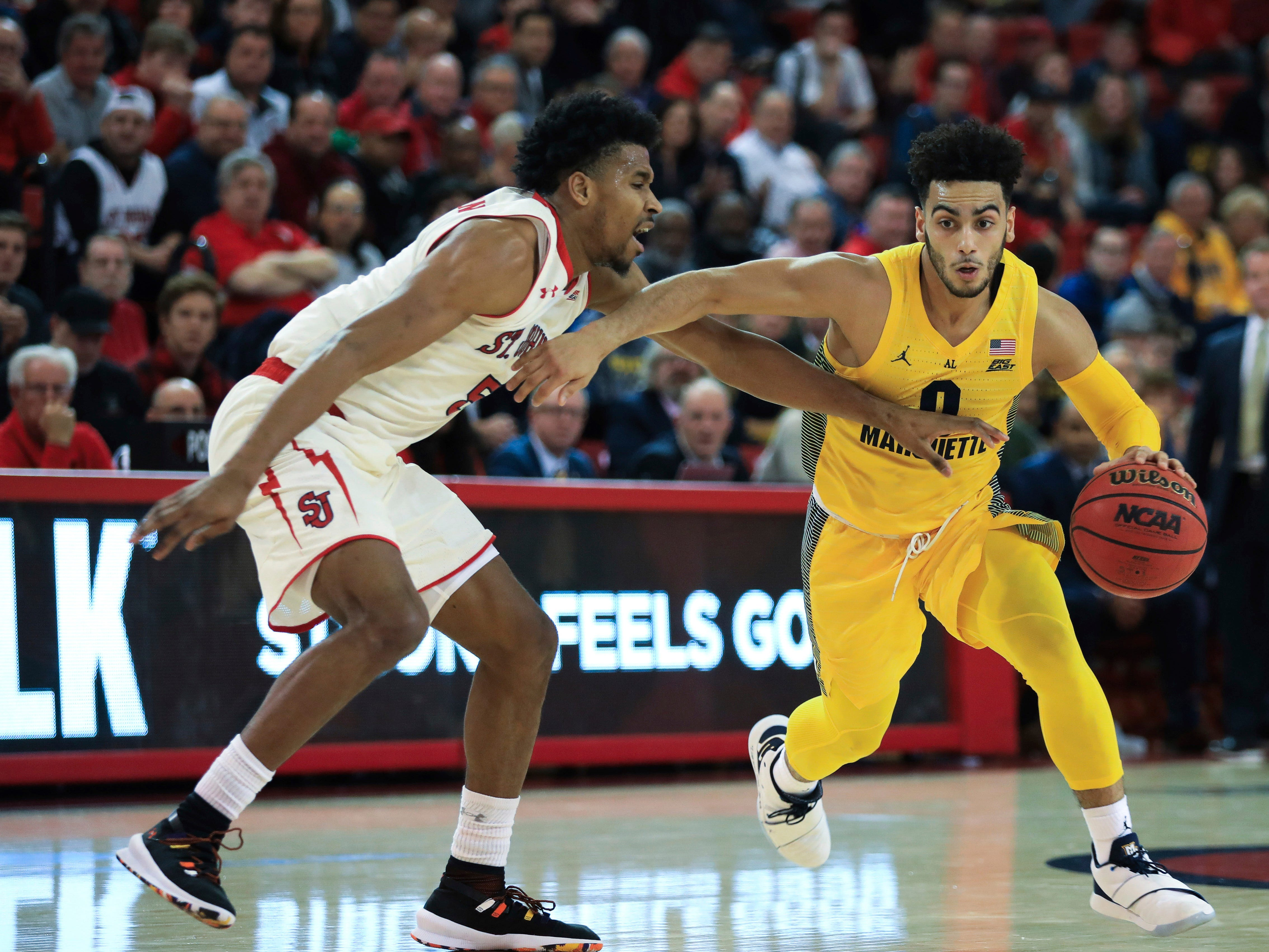Marquette guard Markus Howard drives past St. John's guard Justin Simon during the first half of an NCAA college basketball game Tuesday, Jan. 1, 2019, in New York. (AP Photo/Kevin Hagen). ORG XMIT: NYKH103