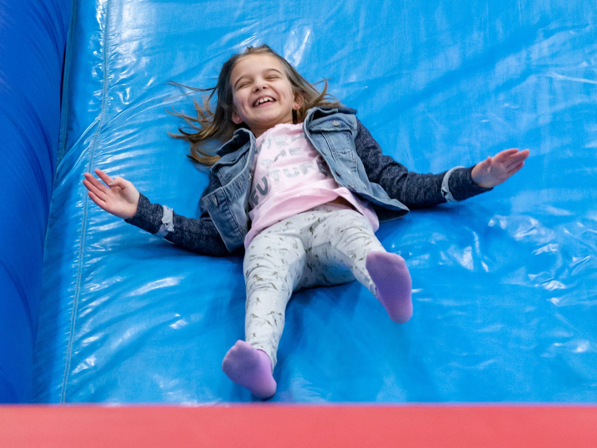 Noelle Petrick, 8, of New Berlin, zips down an inflatable slide during the New Year's Eve Family Night at West Allis Central High School hosted by CAAD - West Allis (the West Allis-West Milwaukee Community Alliance Against Drugs) on Monday evening, Dec. 31, 2018.