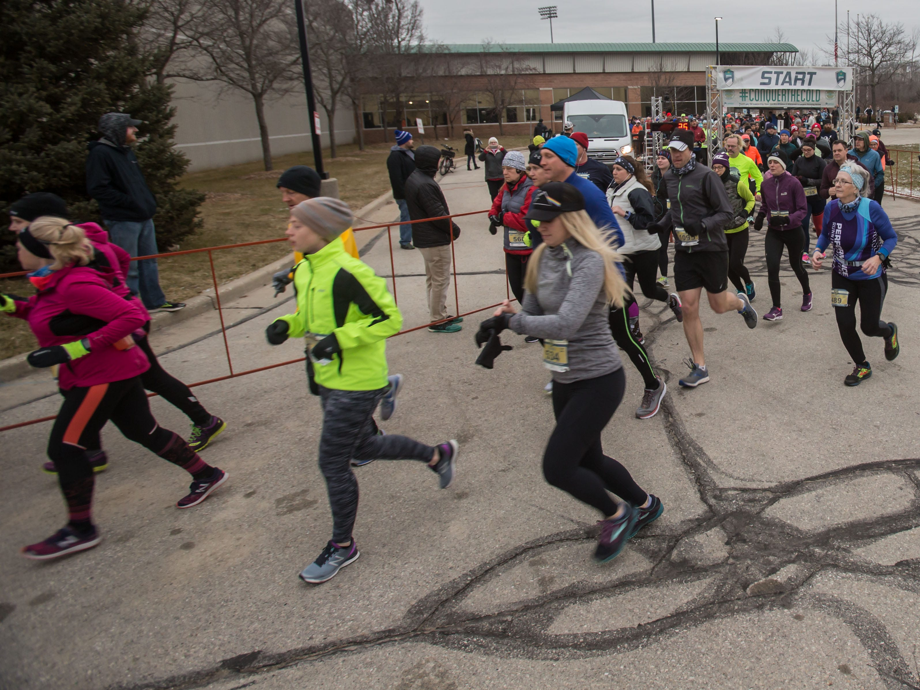 Runners stream past in the 10K race during the 14th annual Run Into the New Year hosted by Lighthouse Events at the Milwaukee County Sports Complex in Franklin on Monday, Dec. 31, 2018.