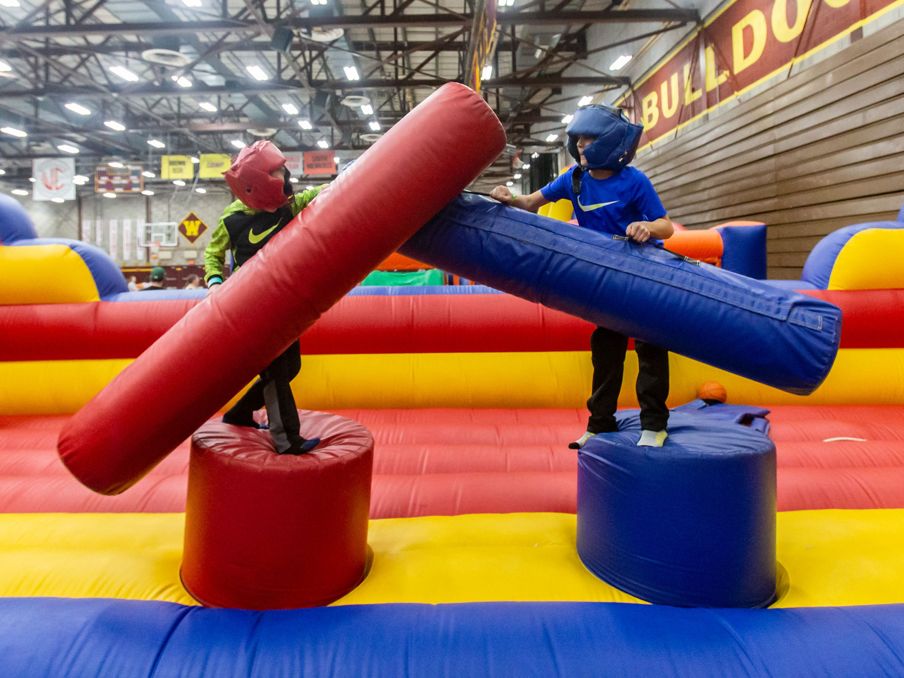 Landon Combs (left), 6, and Jayden Kinder, 10, of Hales Corners, play a jousting game during the New Year's Eve Family Night at West Allis Central High School hosted by CAAD - West Allis (the West Allis-West Milwaukee Community Alliance Against Drugs) on Monday evening, Dec. 31, 2018.