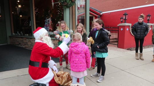 Michael Bukosky (dressed as Santa) and his daughter, Audrey, gave away presents in downtown Oconomowoc to spread holiday cheer.