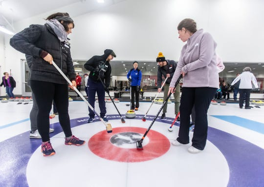 Curling instructor Julia Padvoiskis (center) gives advice on sweeping a stone during the Learn to Curl program at the Milwaukee Curling Club in Cedarburg on Saturday, Dec. 29, 2018.
