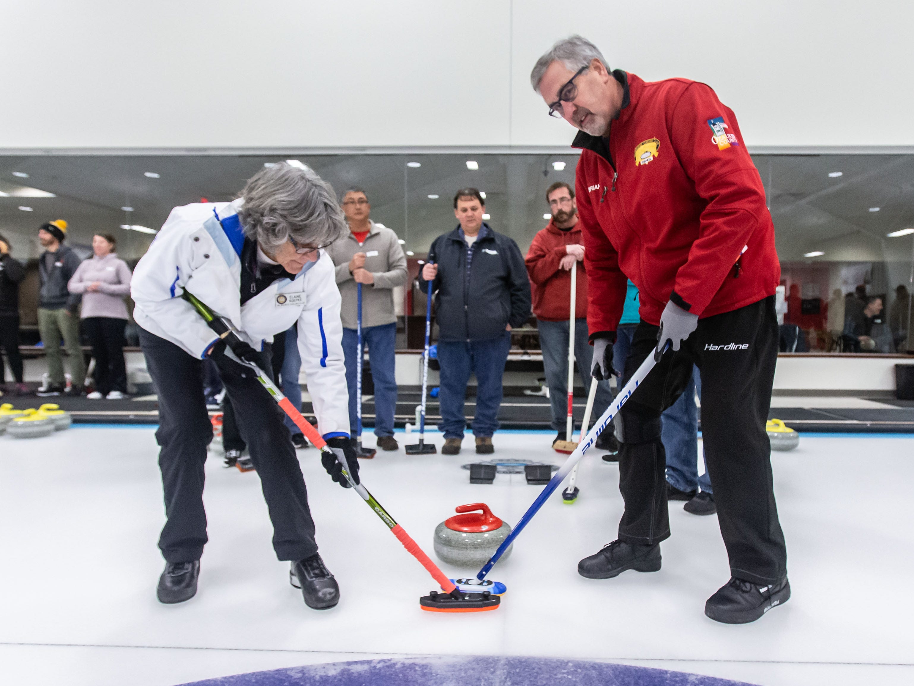 Curling instructors Elaine Koepke and Brian Geiger demonstrate sweeping a stone during the Learn to Curl program at the Milwaukee Curling Club in Cedarburg on Saturday, Dec. 29, 2018.