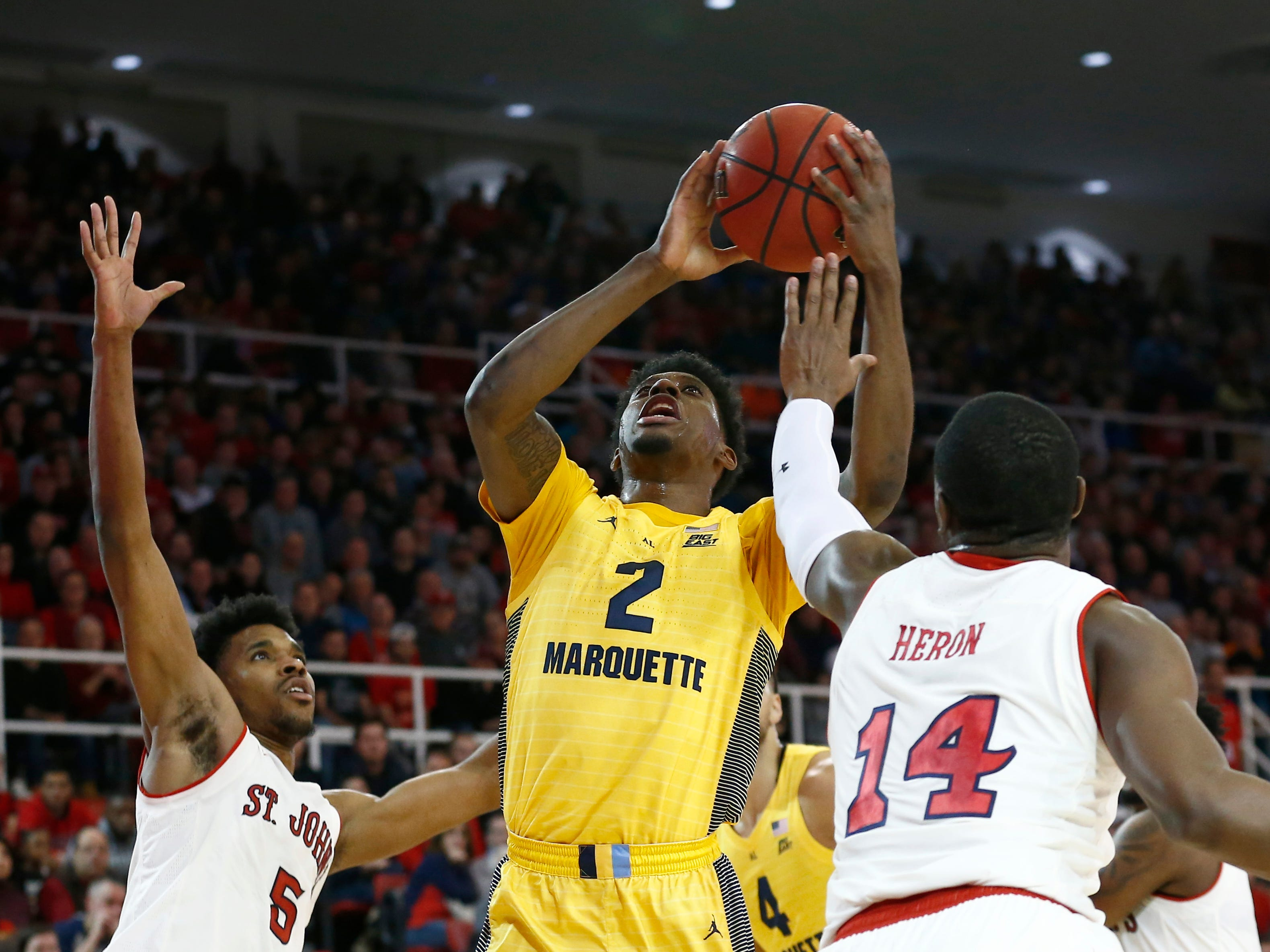 Jan 1, 2019; Queens, NY, USA; Marquette Golden Eagles forward Sacar Anim (2)  shoots against St. John's Red Storm guard Justin Simon (5) and guard Mustapha Heron (14) in the first half at Carnesecca Arena. Mandatory Credit: Nicole Sweet-USA TODAY Sports