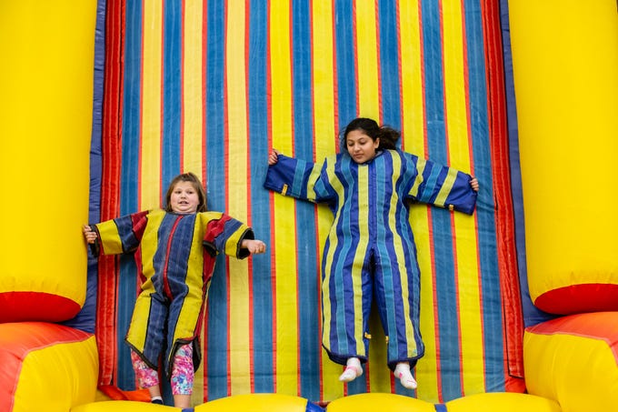 Ten-year-old cousins, Taylor Birk (left) and Ahmyla Paige, of West Allis, adhere themselves to a velcro inflatable during the New Year's Eve Family Night at West Allis Central High School hosted by CAAD - West Allis (the West Allis-West Milwaukee Community Alliance Against Drugs) on Monday evening, Dec. 31, 2018. The event featured games, inflatables, music, swimming, a balloon drop and more.