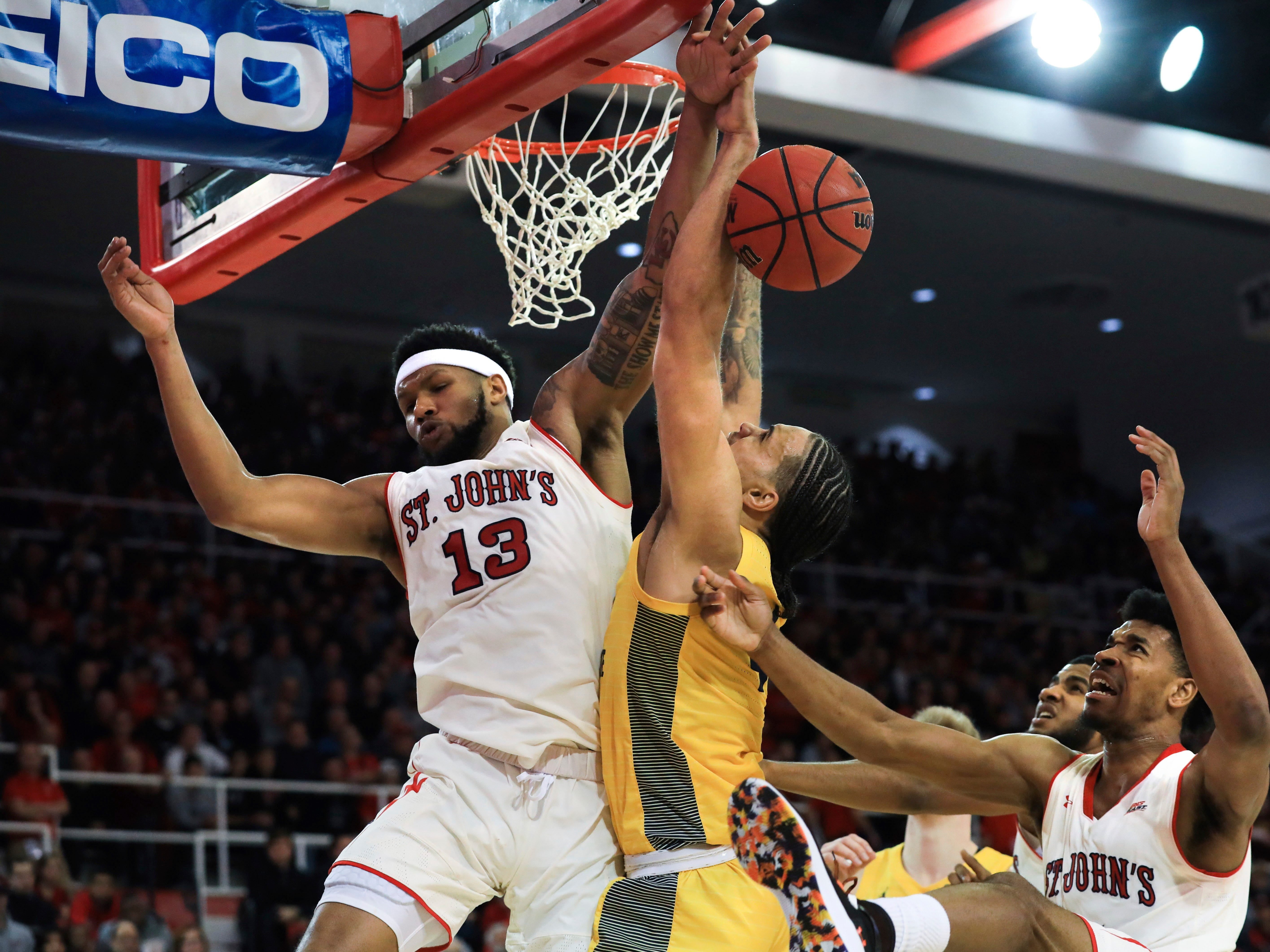 St. John's forward Marvin Clark II blocks a shot from Marquette forward Theo John during the first half of an NCAA college basketball game Tuesday, Jan. 1, 2019, in New York. (AP Photo/Kevin Hagen). ORG XMIT: NYKH104