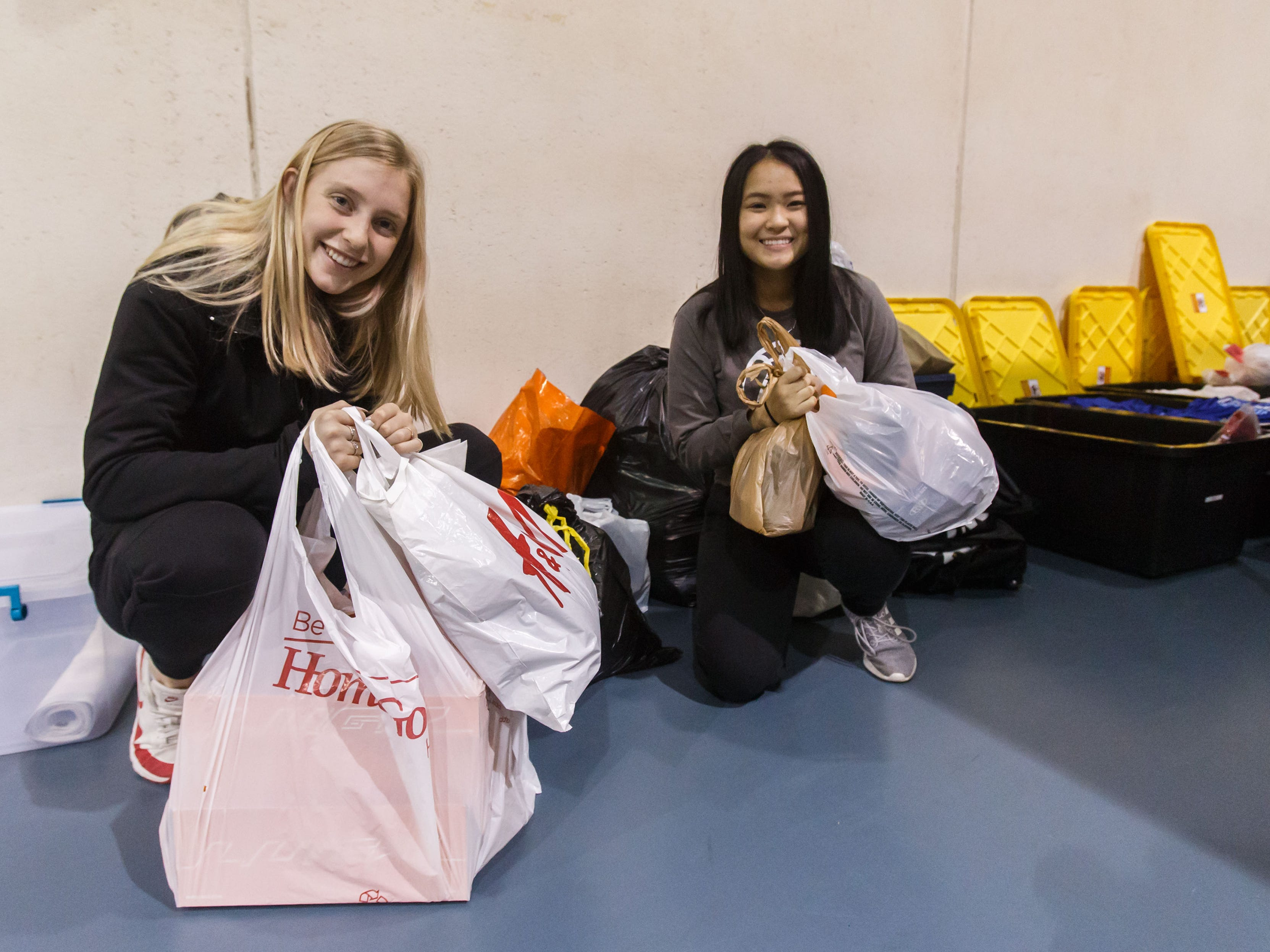 Volunteers Abby Pugh (left) and Vy Pham, both of Franklin, display some of the winter clothing donations collected for the Milwaukee Rescue Mission during the 14th annual Run Into the New Year hosted by Lighthouse Events at the Milwaukee County Sports Complex in Franklin on Monday, Dec. 31, 2018.