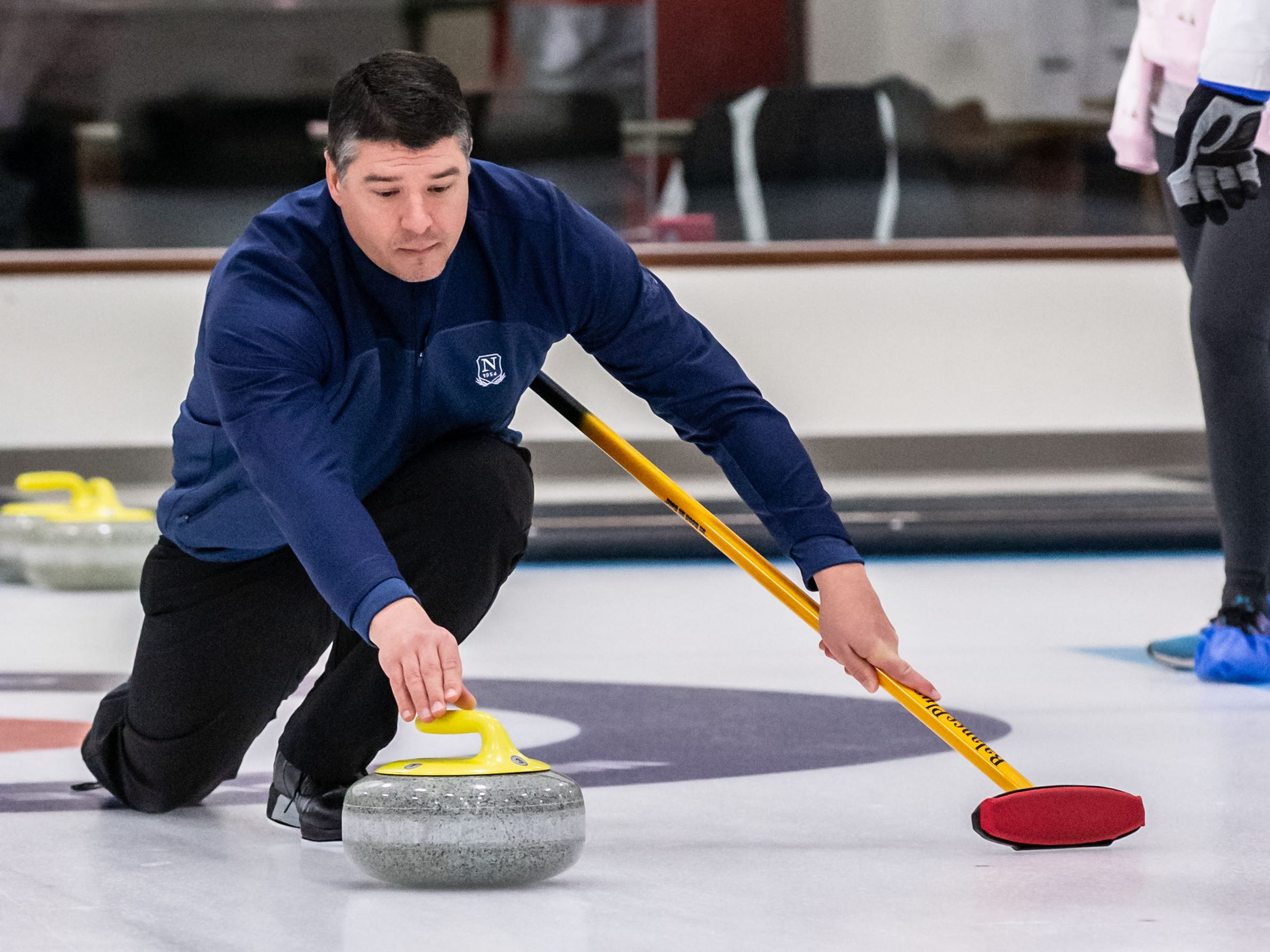 Membership Director Chris Apel demonstrates releasing a stone during the Learn to Curl program at the Milwaukee Curling Club in Cedarburg on Saturday, Dec. 29, 2018.