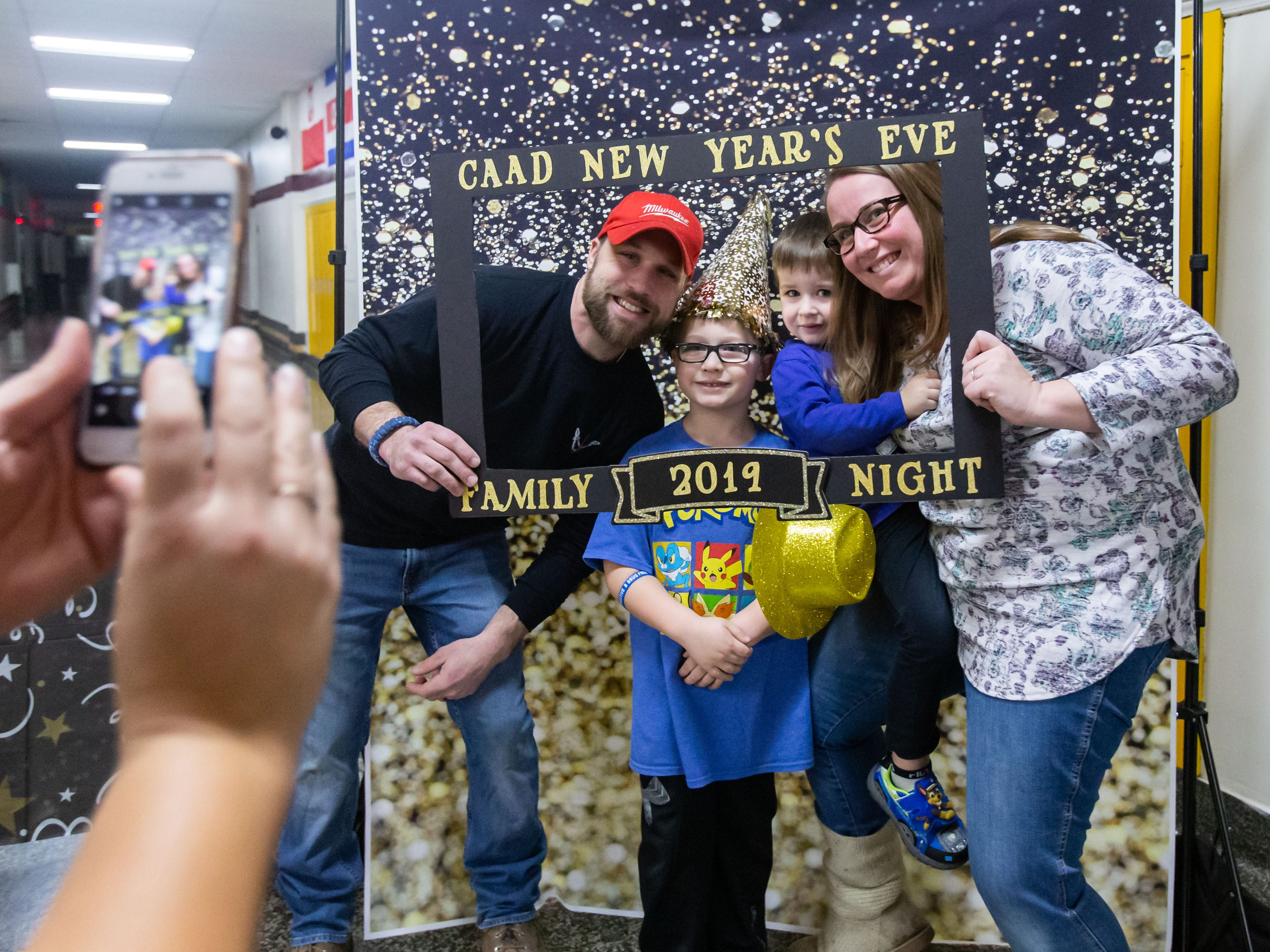 Members of the Roeder family (from left) Erich, Easton, 6, Colton, 3, and Ashley, from West Allis, pose for a photo during the New Year's Eve Family Night at West Allis Central High School hosted by CAAD - West Allis (the West Allis-West Milwaukee Community Alliance Against Drugs) on Monday evening, Dec. 31, 2018. The event featured games, inflatables, music, swimming, a balloon drop and more.