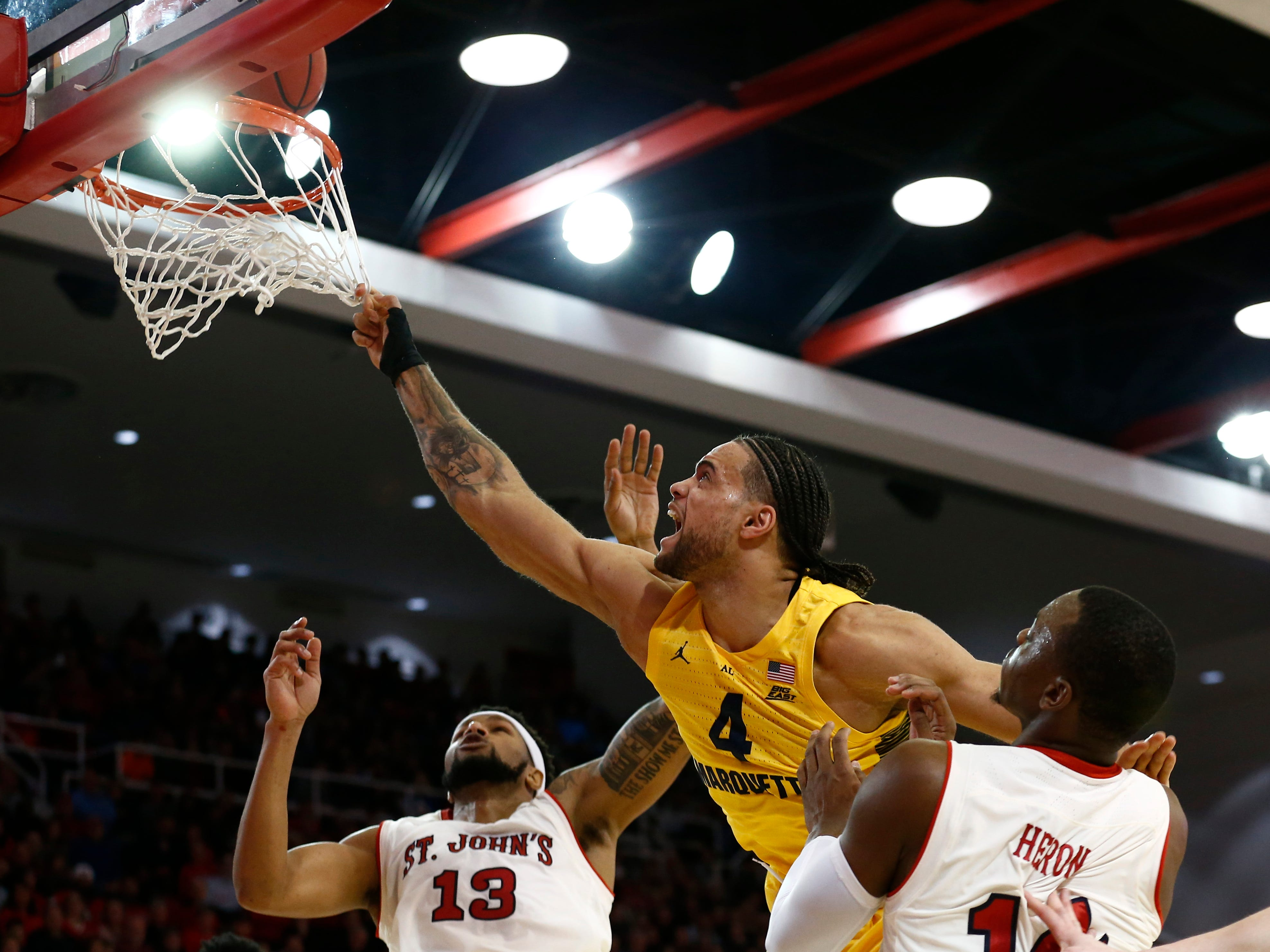 Jan 1, 2019; Queens, NY, USA; Marquette Golden Eagles forward Theo John (4) puts up a shot against St. John's Red Storm forward Marvin Clark II (13) and guard Mustapha Heron (14) in the first half at Carnesecca Arena. Mandatory Credit: Nicole Sweet-USA TODAY Sports