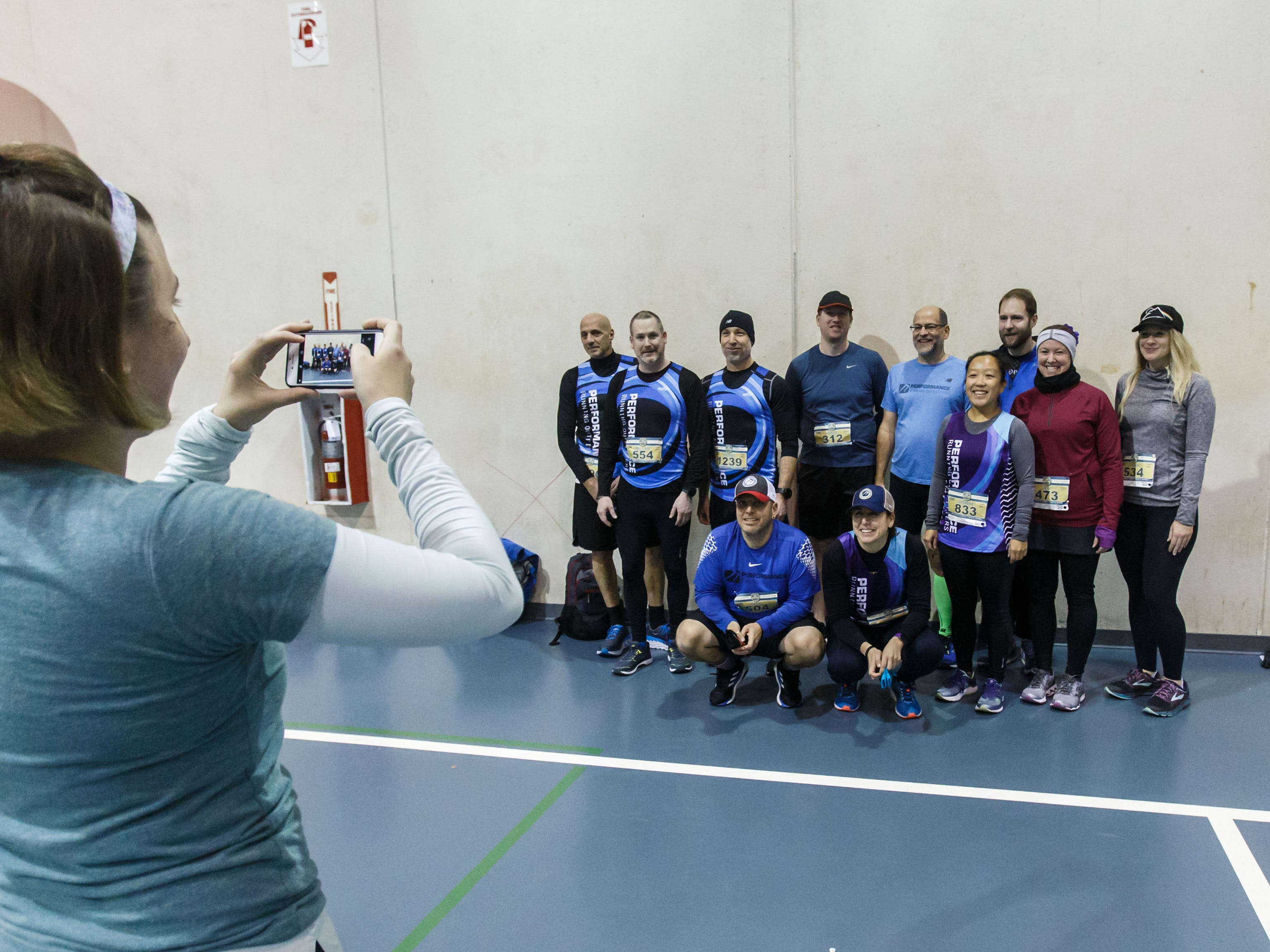 Alison Newcomb of Franklin snaps a photo of her teammates from Performance Running Outfitters prior to the 14th annual Run Into the New Year hosted by Lighthouse Events at the Milwaukee County Sports Complex in Franklin on Monday, Dec. 31, 2018.