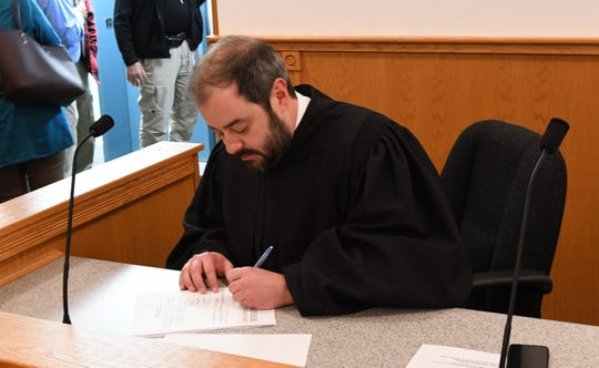 Circuit Court Judge Andrew Bailey signs the oaths of office administered to Baxter County Sheriff's deputies on Tuesday.