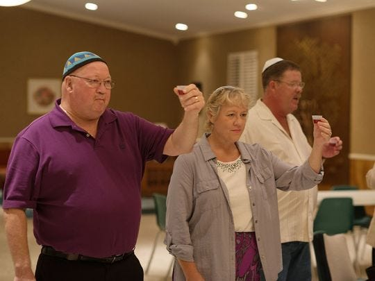 Kenny and Lisa Priddle take part in Oneg Shabbat at Temple Emanu-El in Dothan in this file photo. The Priddle's moved to Dothan to help grow the Jewish community taking part in the stipend program from Blumberg Family Jewish Community Services of Dothan.