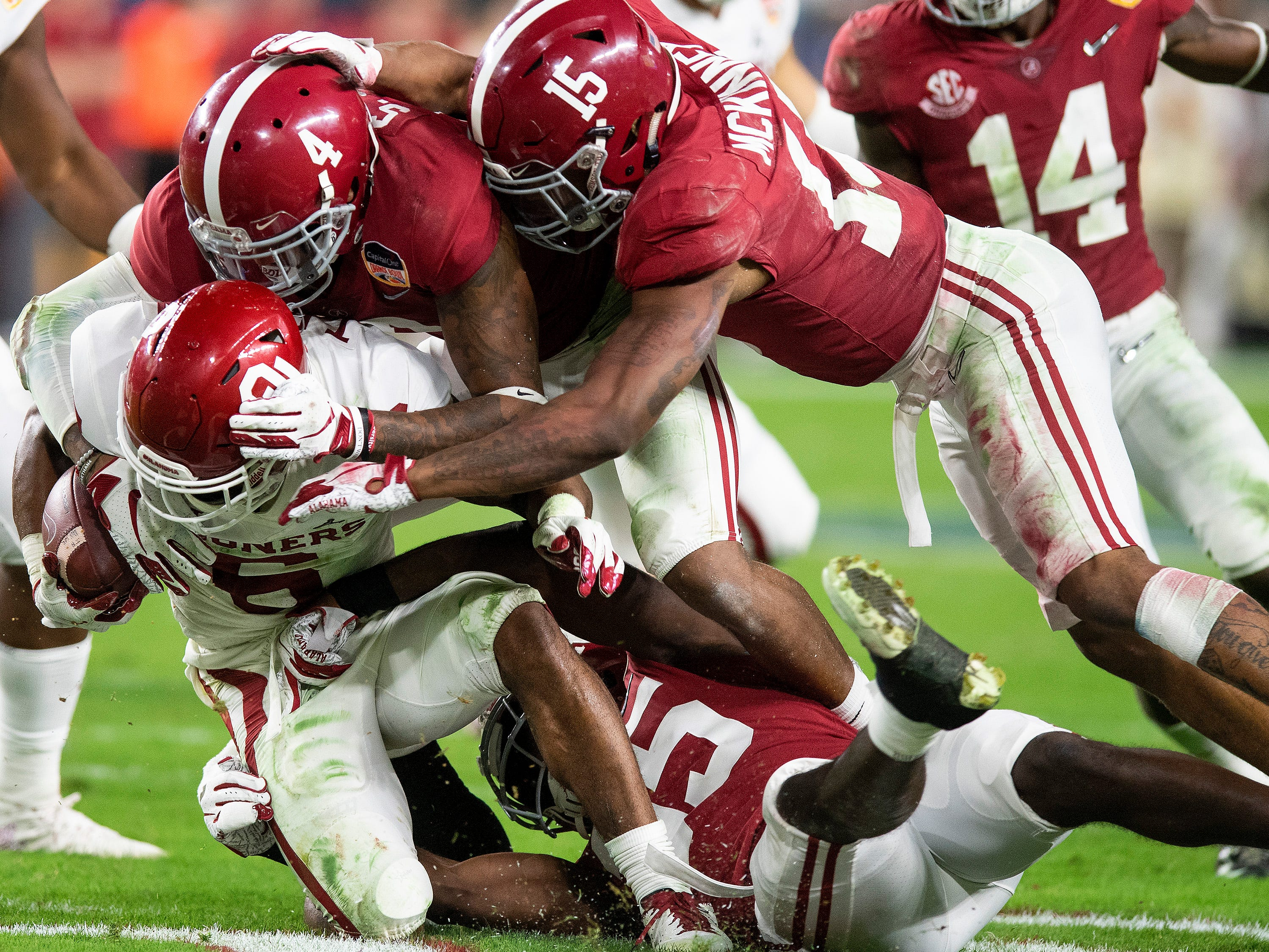 Alabama defensive backs Saivion Smith (4), Xavier McKinney (15) and D.J. Lewis (35) stop Oklahoma 's Tre Brown on a kick return in second half action of the Orange Bowl at Hard Rock Stadium in Miami Gardens, Fla., on Saturday December 29, 2018.