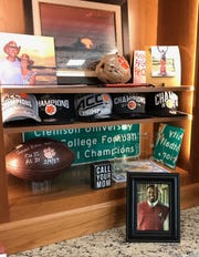 A photo of former Alabama player Victor Ellis rests on Clemson coach Dabo Swinney's desk in his office - next to the game ball when Clemson defeated Alabama for the national title in 2017.