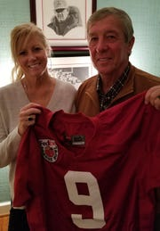Tim and Kathy Miller with Victor's Alabama jersey.