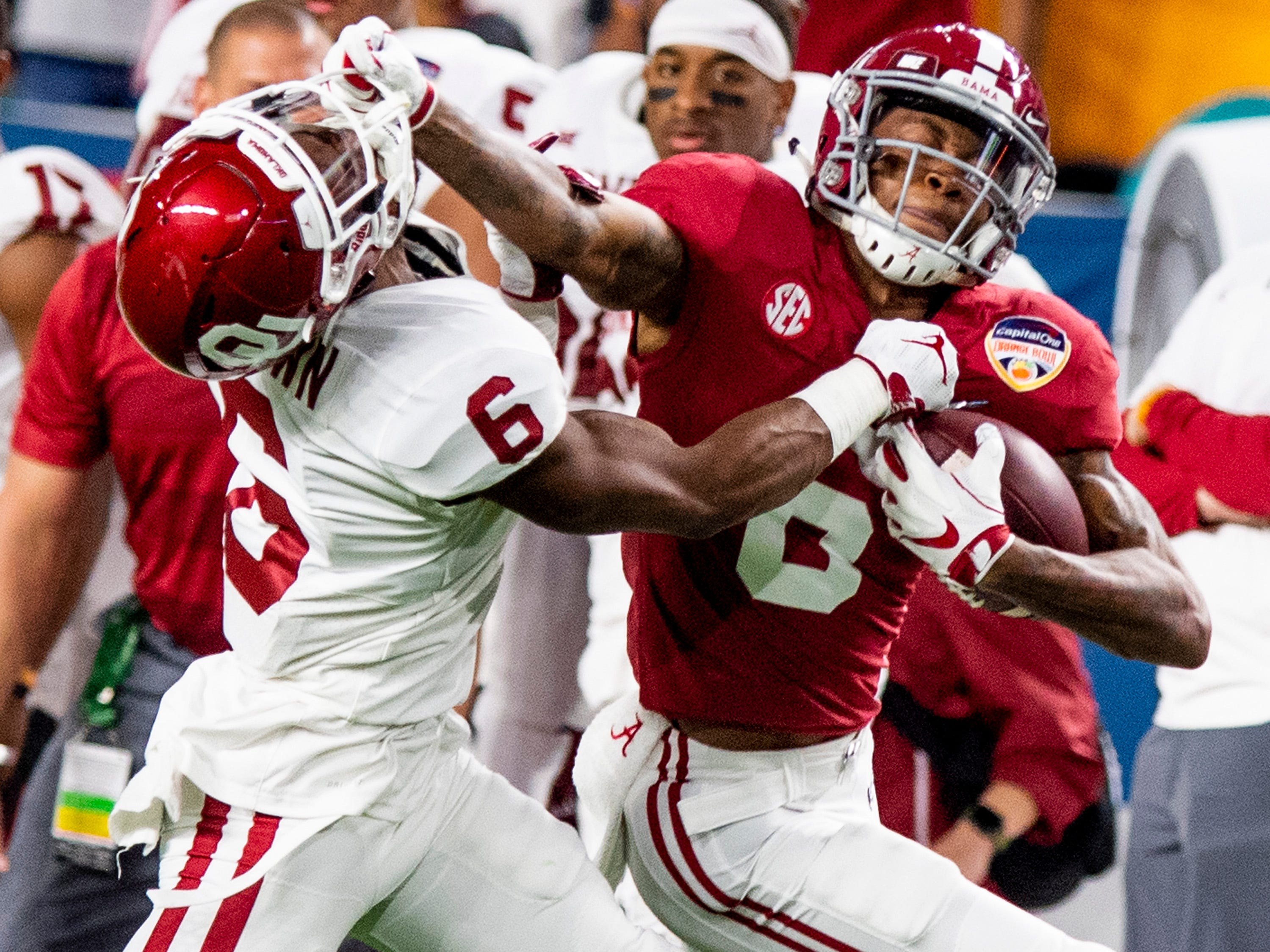 Alabama wide receiver DeVonta Smith (6) fights the tackle of Oklahoma cornerback Tre Brown (6) in first half action of the Orange Bowl at Hard Rock Stadium in Miami Gardens, Fla., on Saturday December 29, 2018.