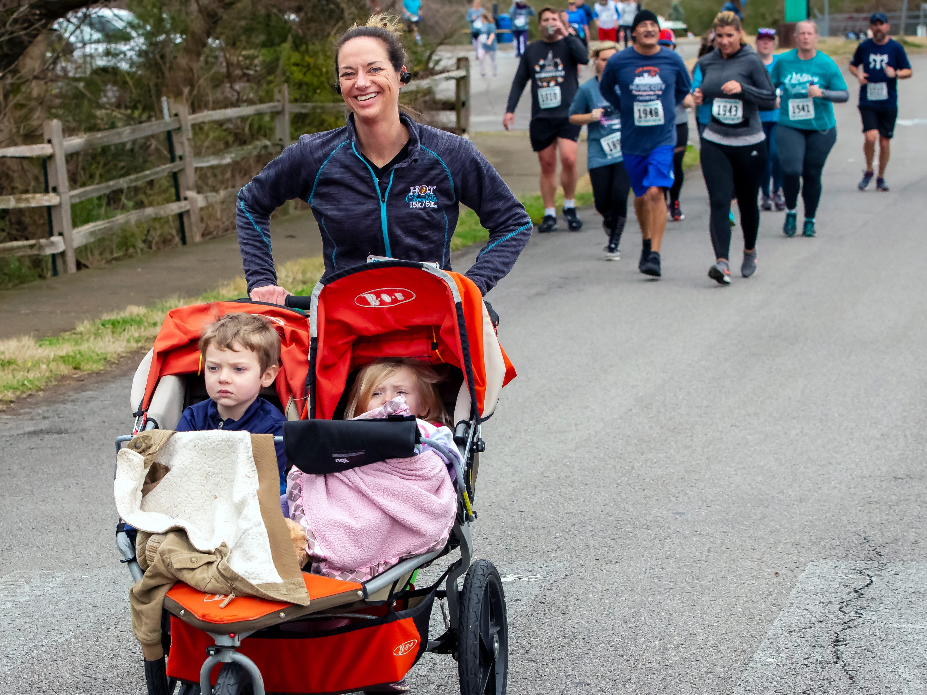 Neely Embree pushes her children near the halfway point the New Years Day 5K event held at Old Fort Park on Jan. 1, 2019.