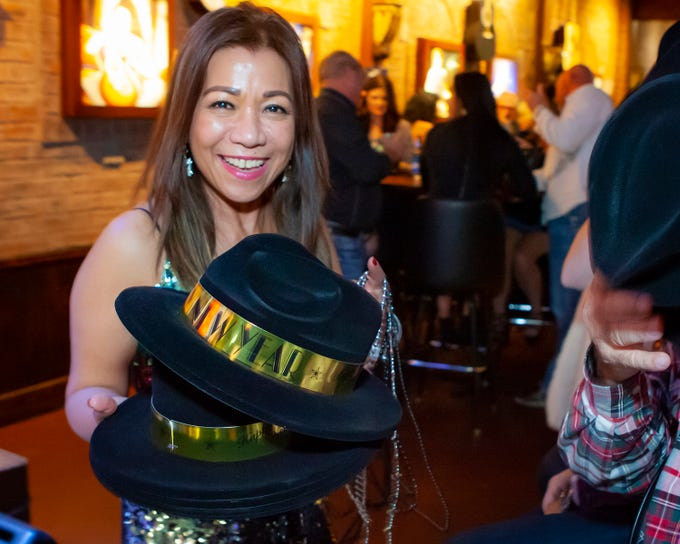Owner Gina Strode hands out hats to revelers at the New Year's party at Hank's Honky Tonk in Murfreesboro.
