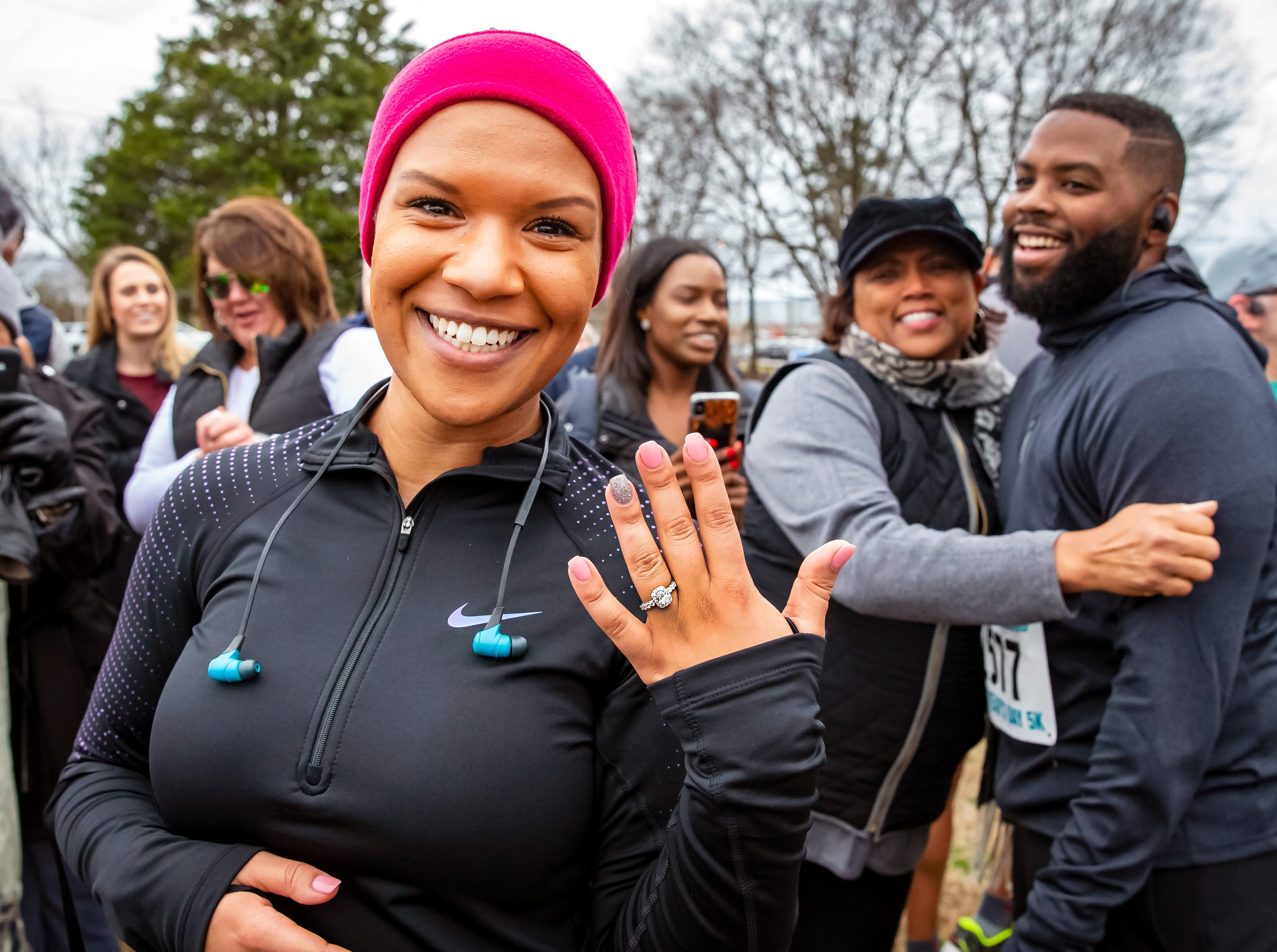 Newly engaged Tiffany Smith shows her new ring as boyfriend Joshua Crutchfield (background) is congratulated by friends. Crutchfield proposed after the couple finished the New Year's Day 5K event held at Old Fort Park on Jan 1, 2019. photo by Jim Davis/M'Boro Parks & Rec.