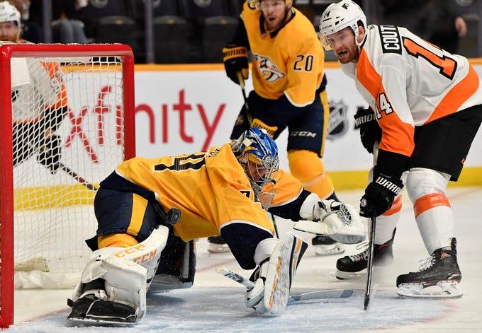Predators goaltender Juuse Saros (74) blocks a shot by Flyers center Sean Couturier (14) during the second period at Bridgestone Arena Tuesday, Jan. 1, 2019, in Nashville, Tenn.