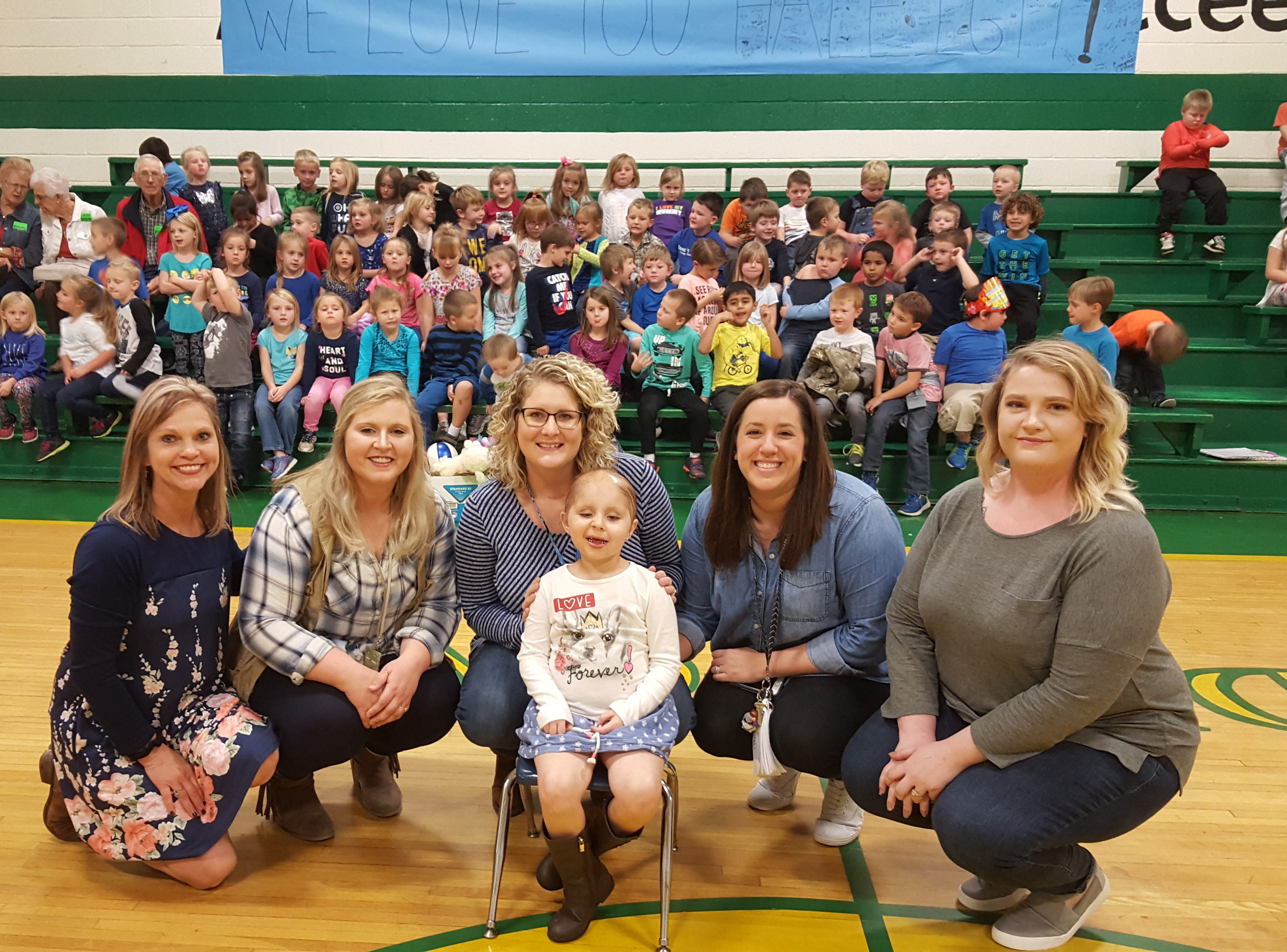 """East Cheatham Elementary School teachers smile with Kindergartener Haleigh Peden at a """"Haleigh's Day"""" assembly, organized to support her before heading to St. Jude."""