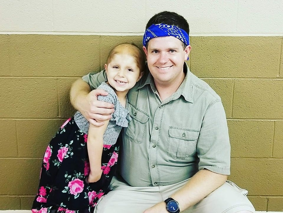 Haleigh Peden, 5, smiles with her youth pastor Tyler Binkley, of Bearwallow Road Church of Christ. Binkley started a Facebook group called Haleigh's Warriors to update the community on her progress as she battles a rare cancer, and for the community to leave encouraging messages for Haleigh.